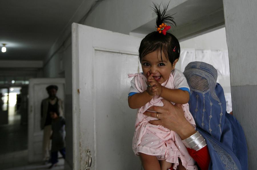 An Afghan girl reacts as she arrives with her mother for treatment in the local hospital of Feyzabad, September 28, 2008.