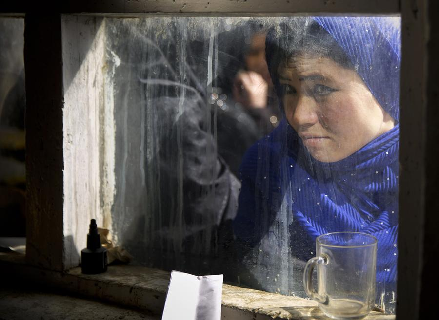 An Afghan woman peers through a window where women line up to have their picture taken to register for the upcoming presidential elections in a school in Kabul, March 18, 2014.
