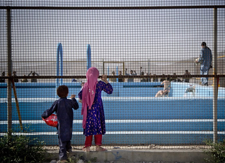 Afghan children peer through a fence that surrounds a swimming pool on a hill overlooking Kabul, Afghanistan, May 2013.