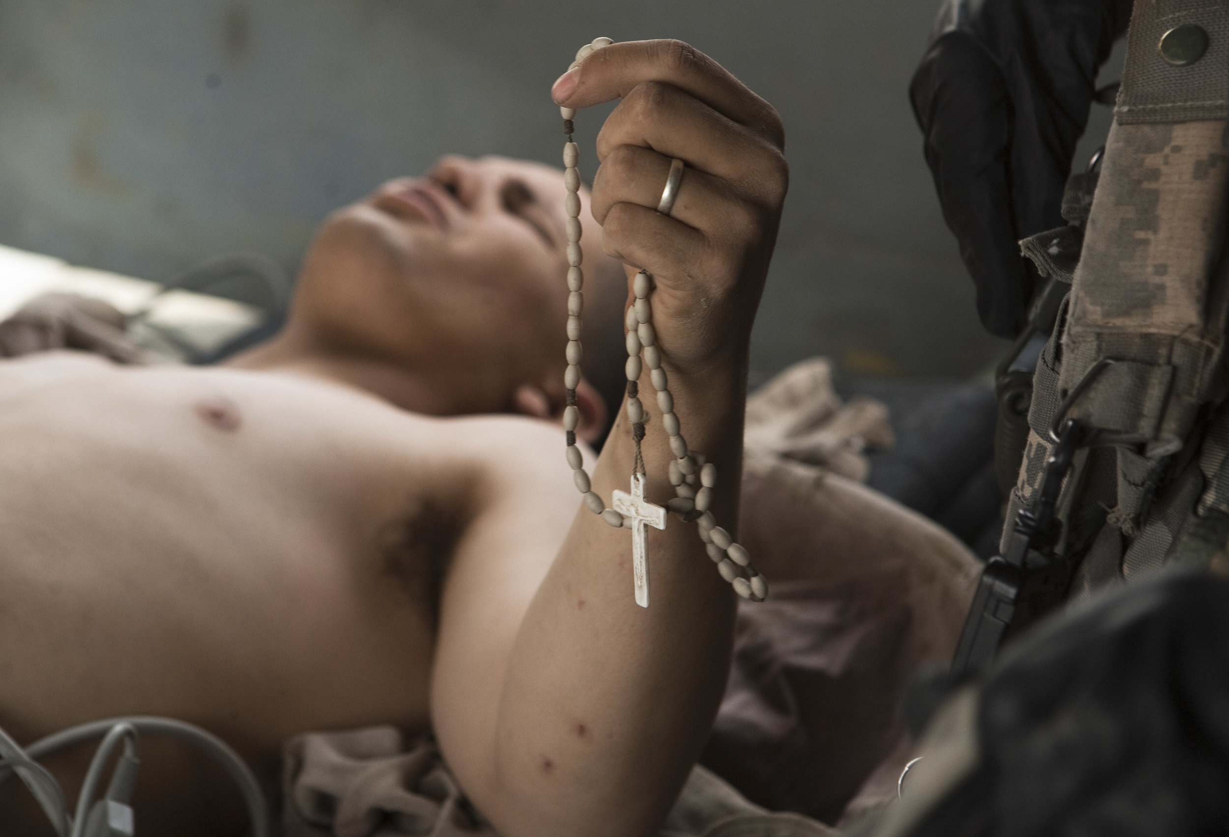 Lance Cpl. Blas Trevino of the 1st Battalion, 5th Marines, clinches onto his Rosary as he's rescued onto a medevac helicopter after getting shot in the stomach near Sangin, Afghanistan, June 11, 2011.