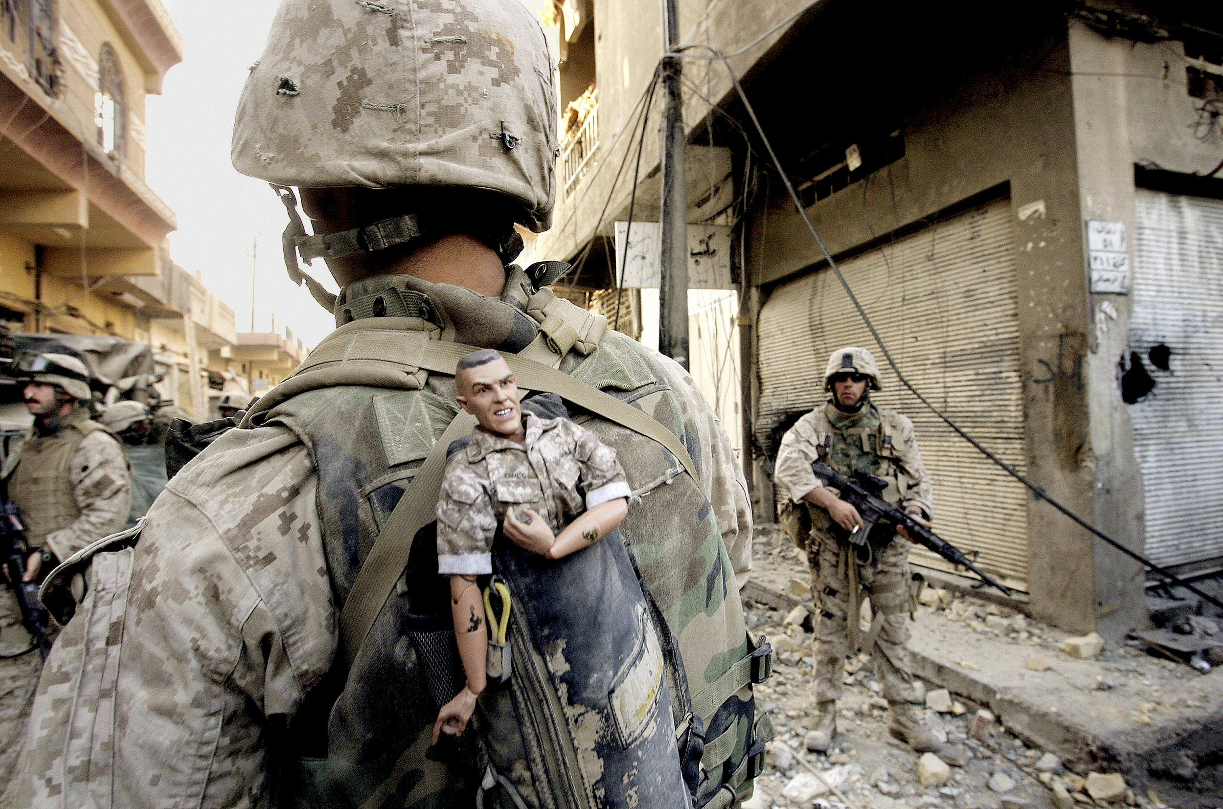 A U.S. Marine carrying a good luck mascot in western Fallujah, Iraq, November 14, 2004.