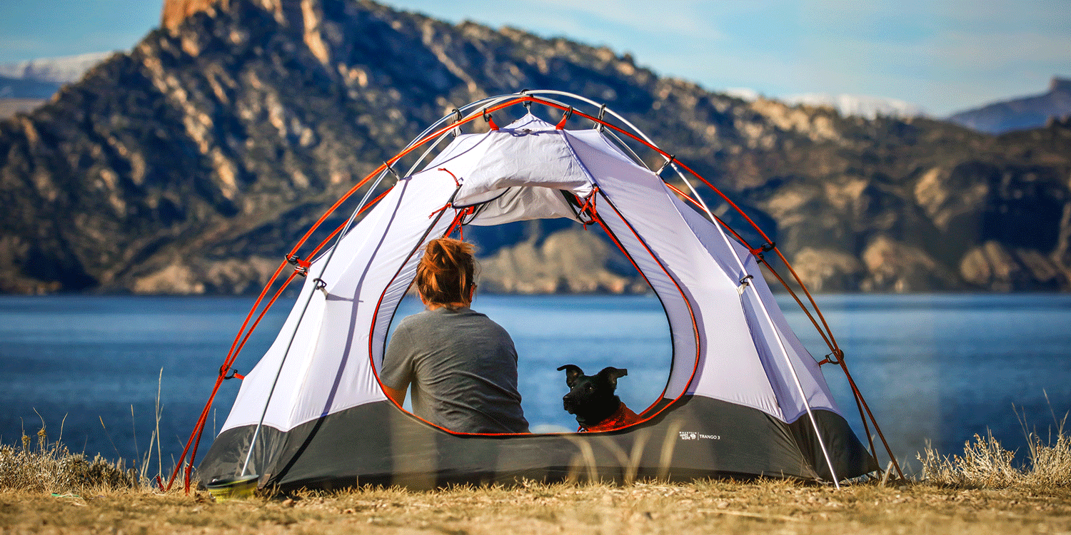 Women camping in the mountains by a river with her dog - who would use Shower in a Can instead of wet wipes