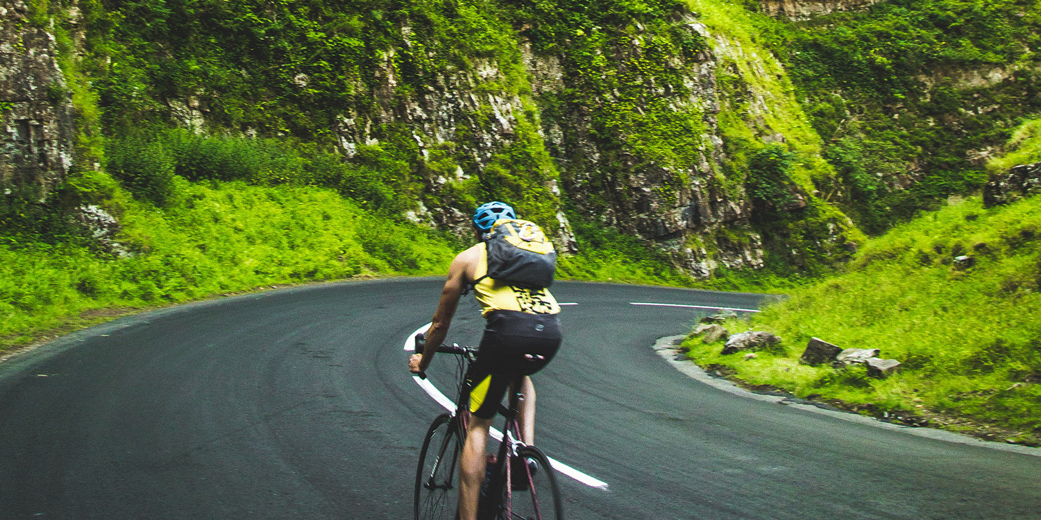 Male road cyclist in lush green mountains - he would use Shower in a Can as a dry shower to get clean and fresh