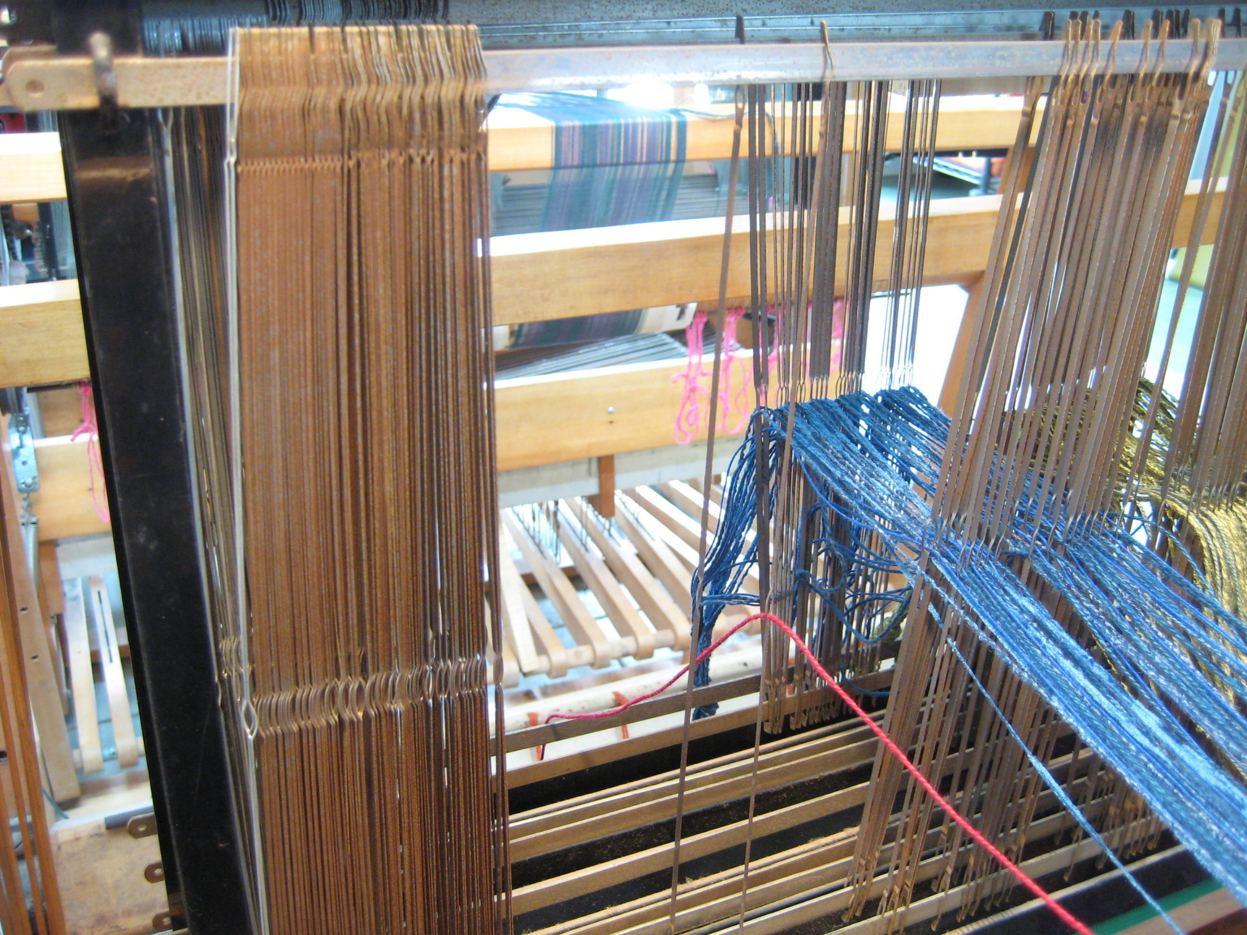 On this loom, the heddles are made of medal and are the type used by commercial production looms. It is very easy to make a mistake, so I count out the heddles I use in a section and then check them after that section is threaded. Each section is tied in a hard knot after threading.