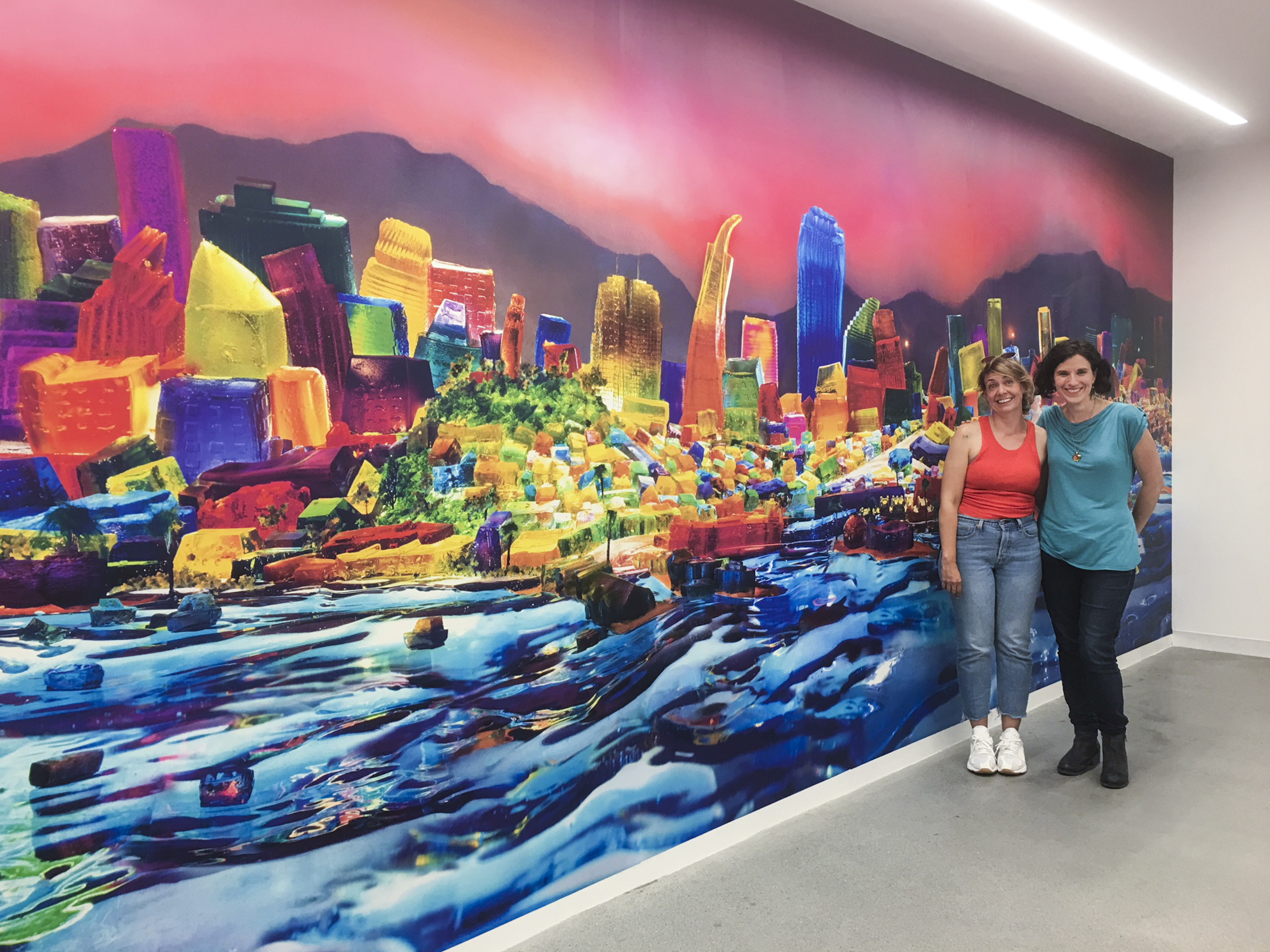 """Kristin Farr and Liz Hickok with her installation of her mural """"View From Alcatraz"""" from the """"San Francisco in Jell-O"""" series."""
