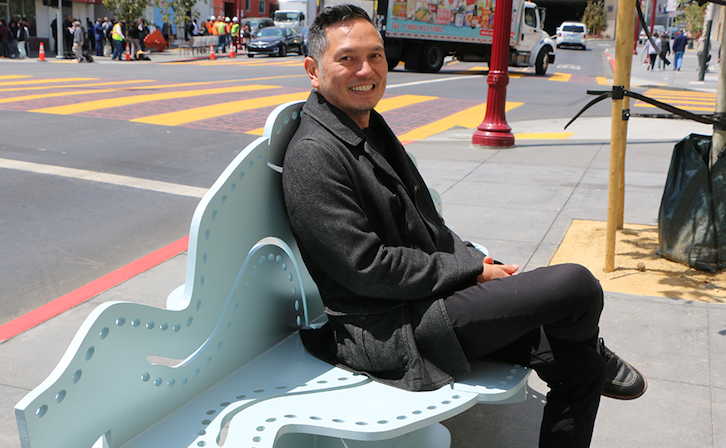 Michael Arcega on a cloud-shaped bench he created for the Broadway Chinatown Streetscape Improvement Project. Photo by Jamie Oppenheim.