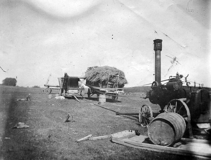 Bill Austin's machine set up to thresh near red barn