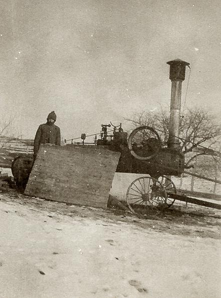 Bill Austin's threshing machine set up near red barn