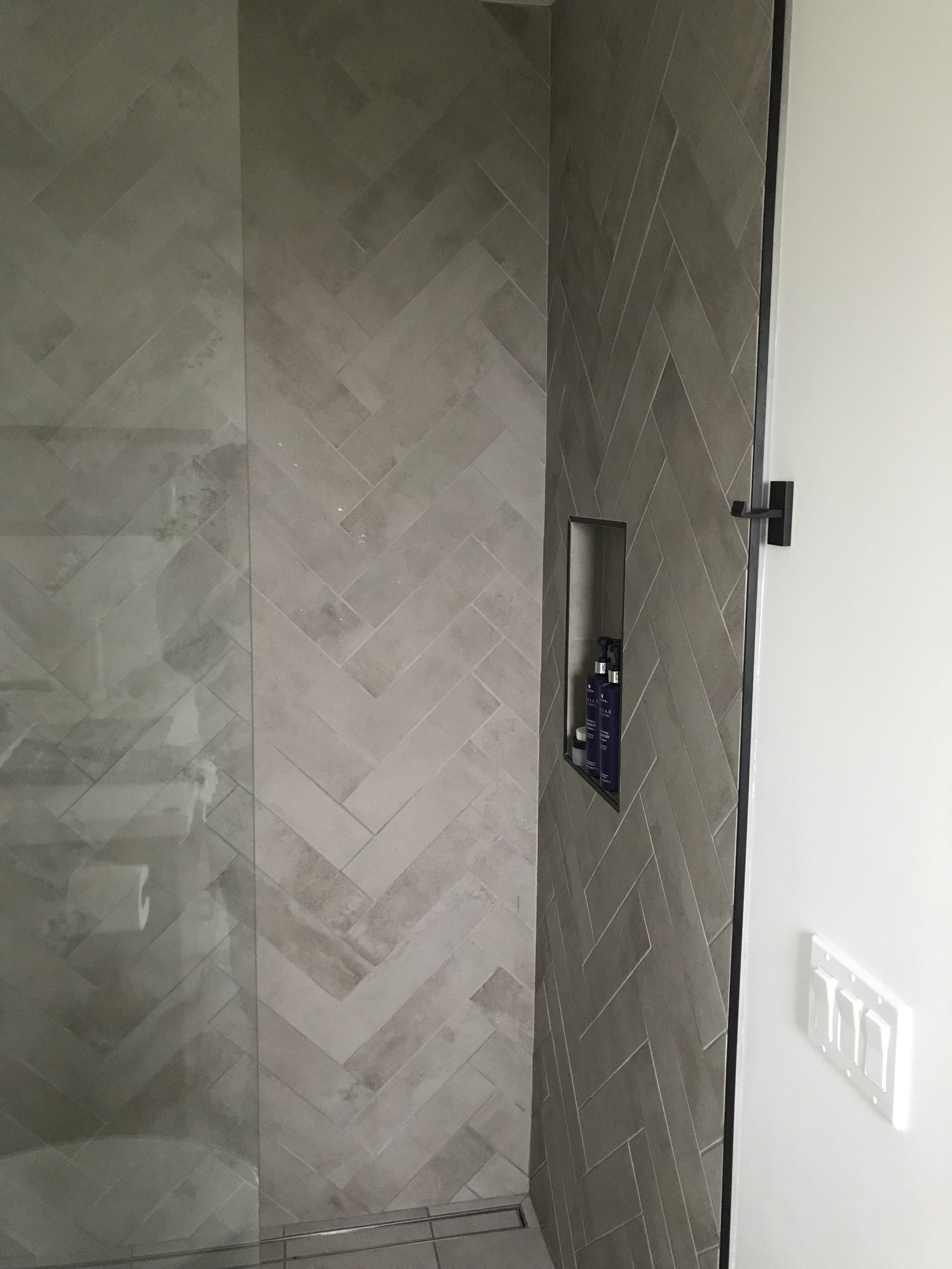 The shower walls are covered in Italian tiles laid in a herringbone pattern and is enclosed with a floor to ceiling single pane of glass.