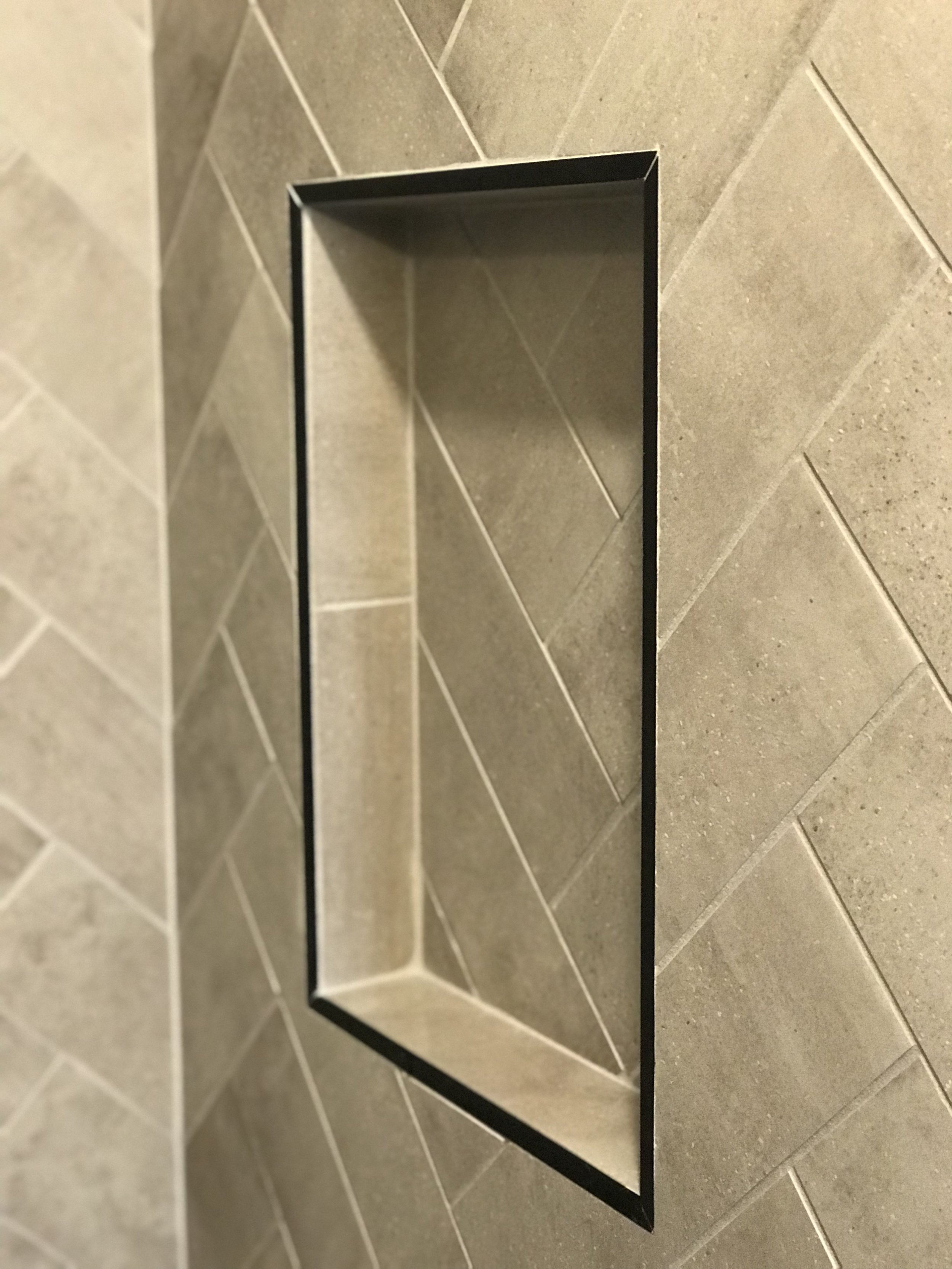 Shower niche - edges are finished off with black Schluter.