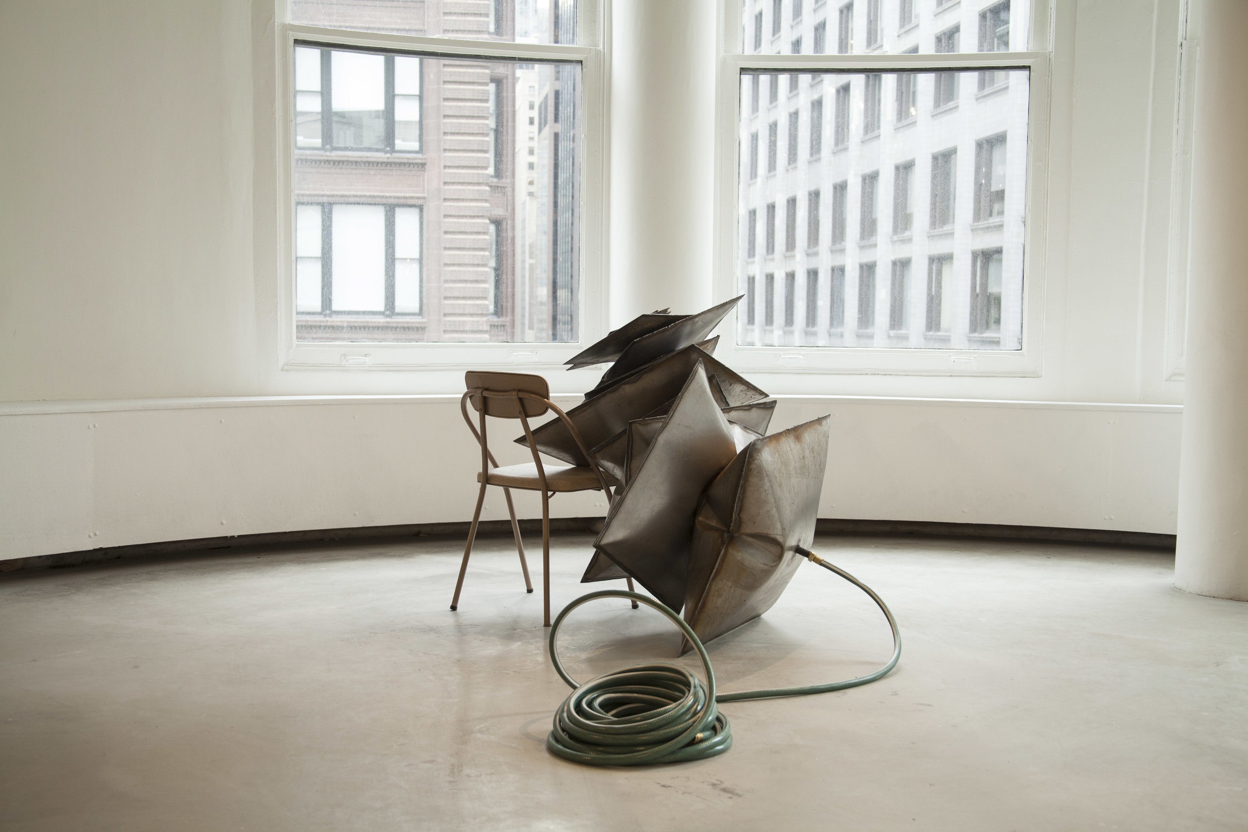 Unnamed Object       (accordion to whom?)  , pressure inflated steel, garden hose, chair,   2015