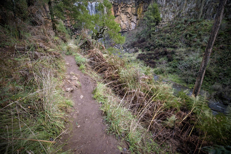 The main narrow dirt path that hugs the cliffs edge. A steep drop to the river below.