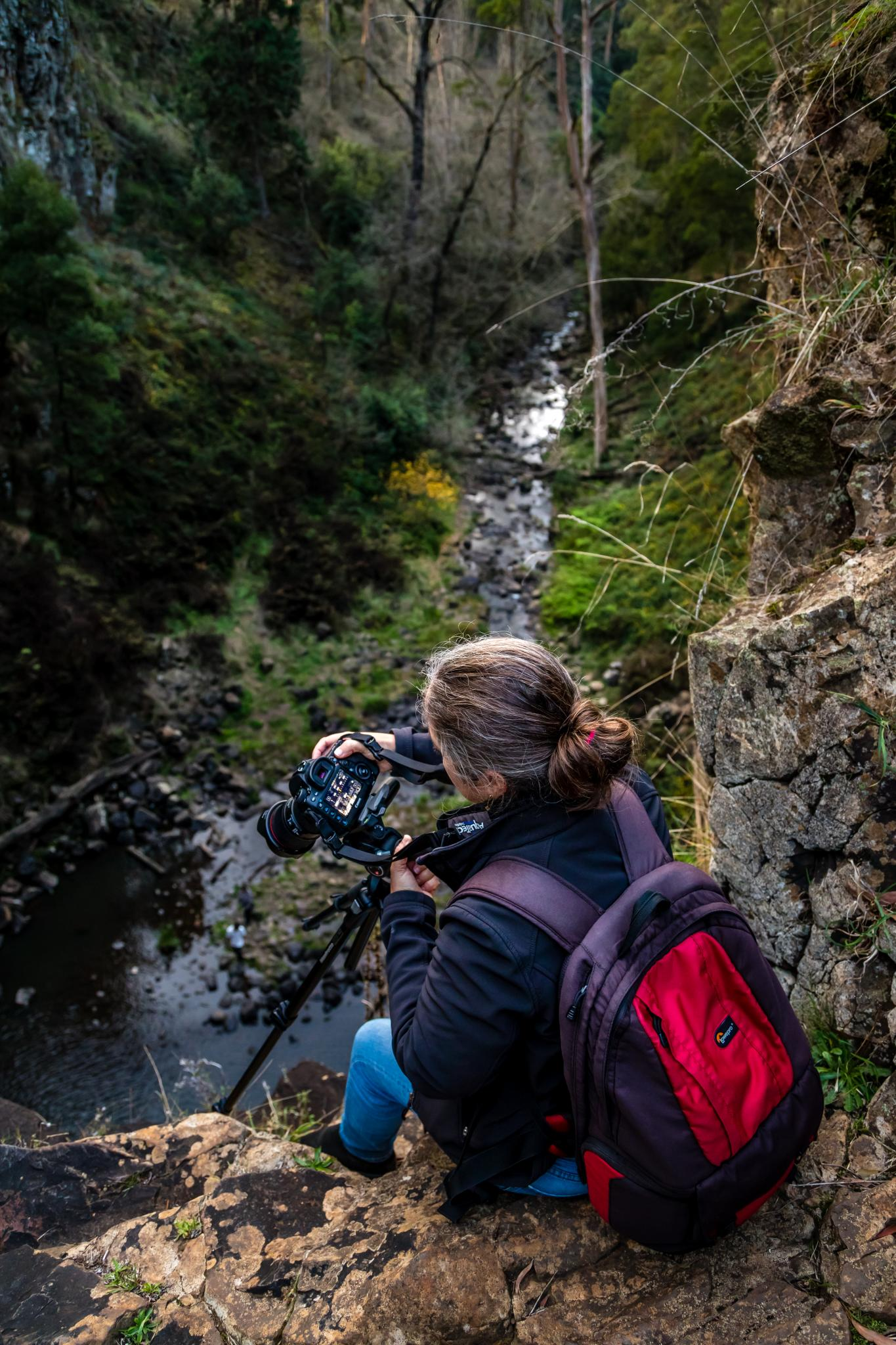 A photographer sits on the edge of the falls. the falls are a 32 metre drop to the river bed below.  Russell Charters Images. This work is licensed under Creative Commons.  https://www.flickr.com/photos/russellcharters/27560443307