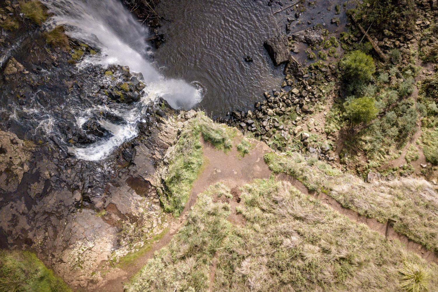 The view from the air. This shows the paths along the highly unstable edge. There is remnants of an old fence that has since collapsed to the falls below. The cleared section marks a popular selfie point.