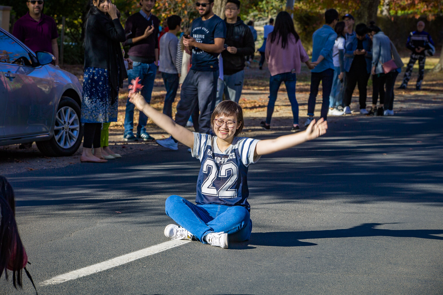 A visitor sits in the middle of the road posing for her trophy image of Macedon.