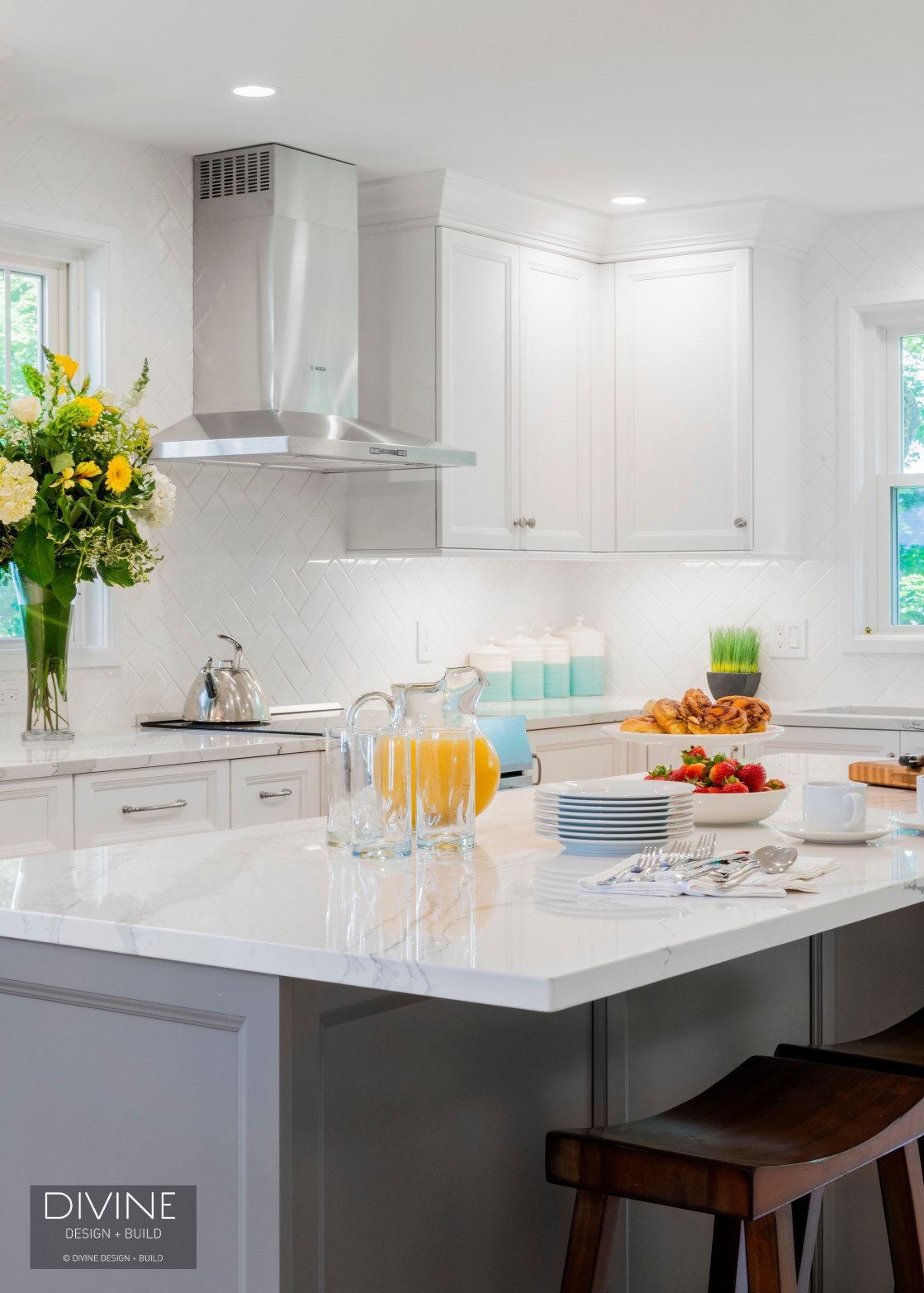 Transitional style kitchen with white and grey shaker cabinets. White subway tile backsplash in herringbone pattern. Calacatta countertops.
