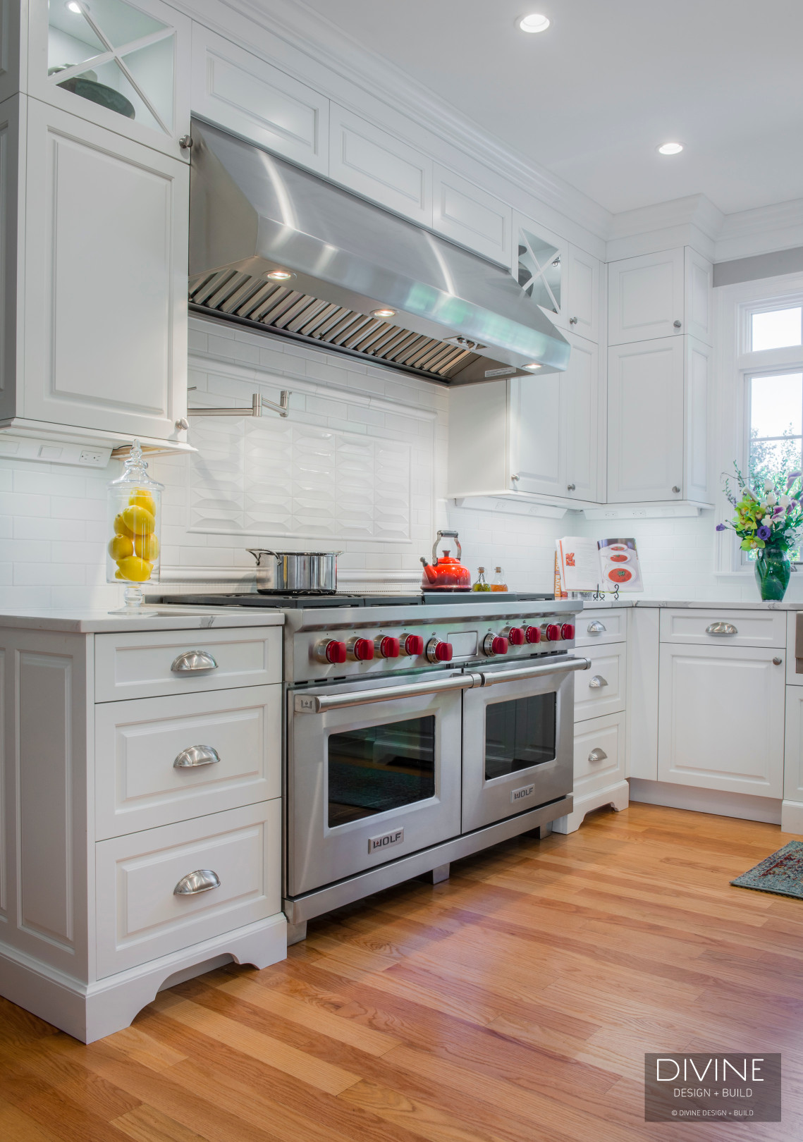 Traditional kitchen with grey and white cabinets. Calacatta countertops and commercial wolf range. Column wine fridge.