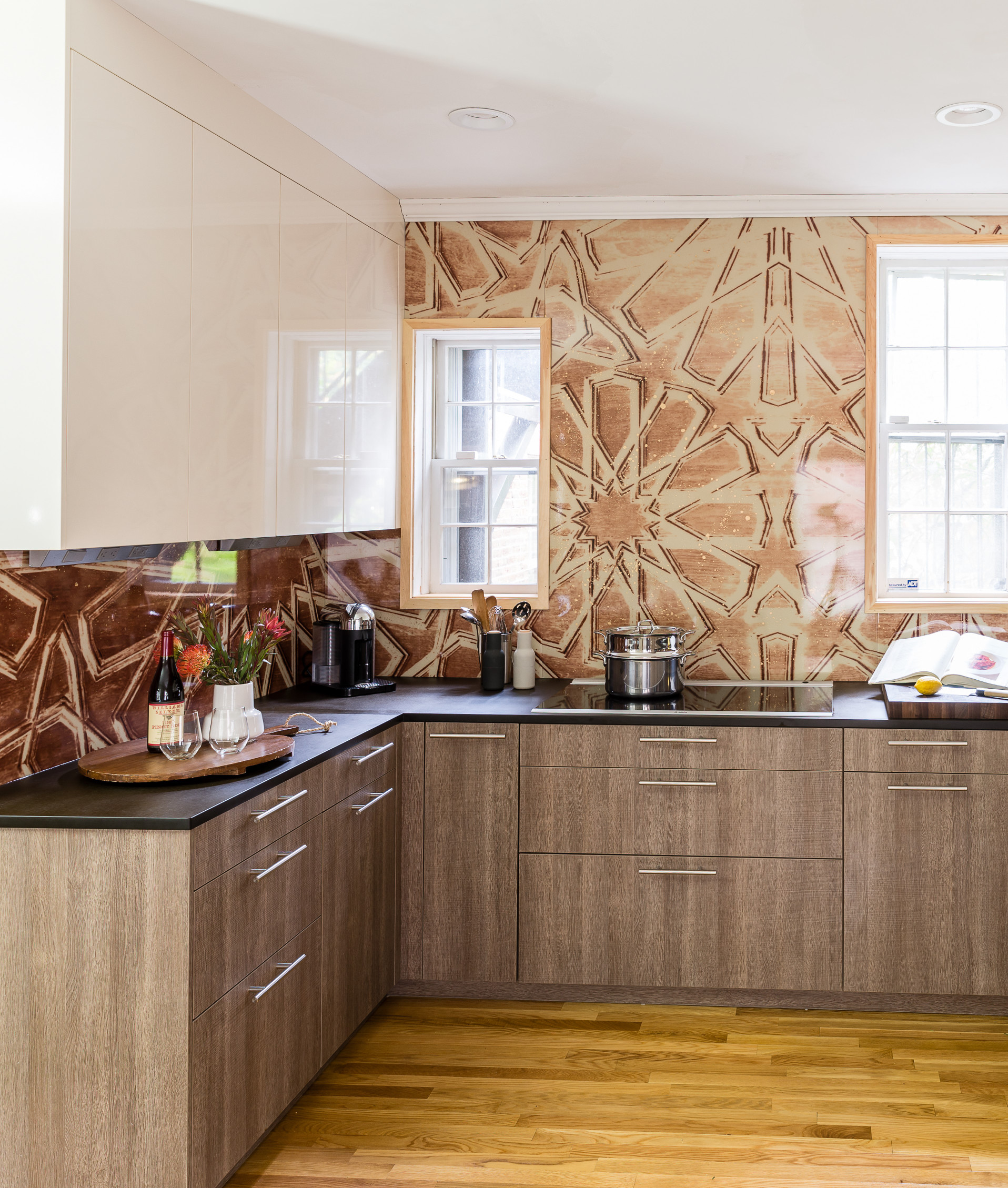Moroccan style backsplash with oak veneer leicht cabinets in a modern kitchen. Wolf appliances, and a column wine fridge.