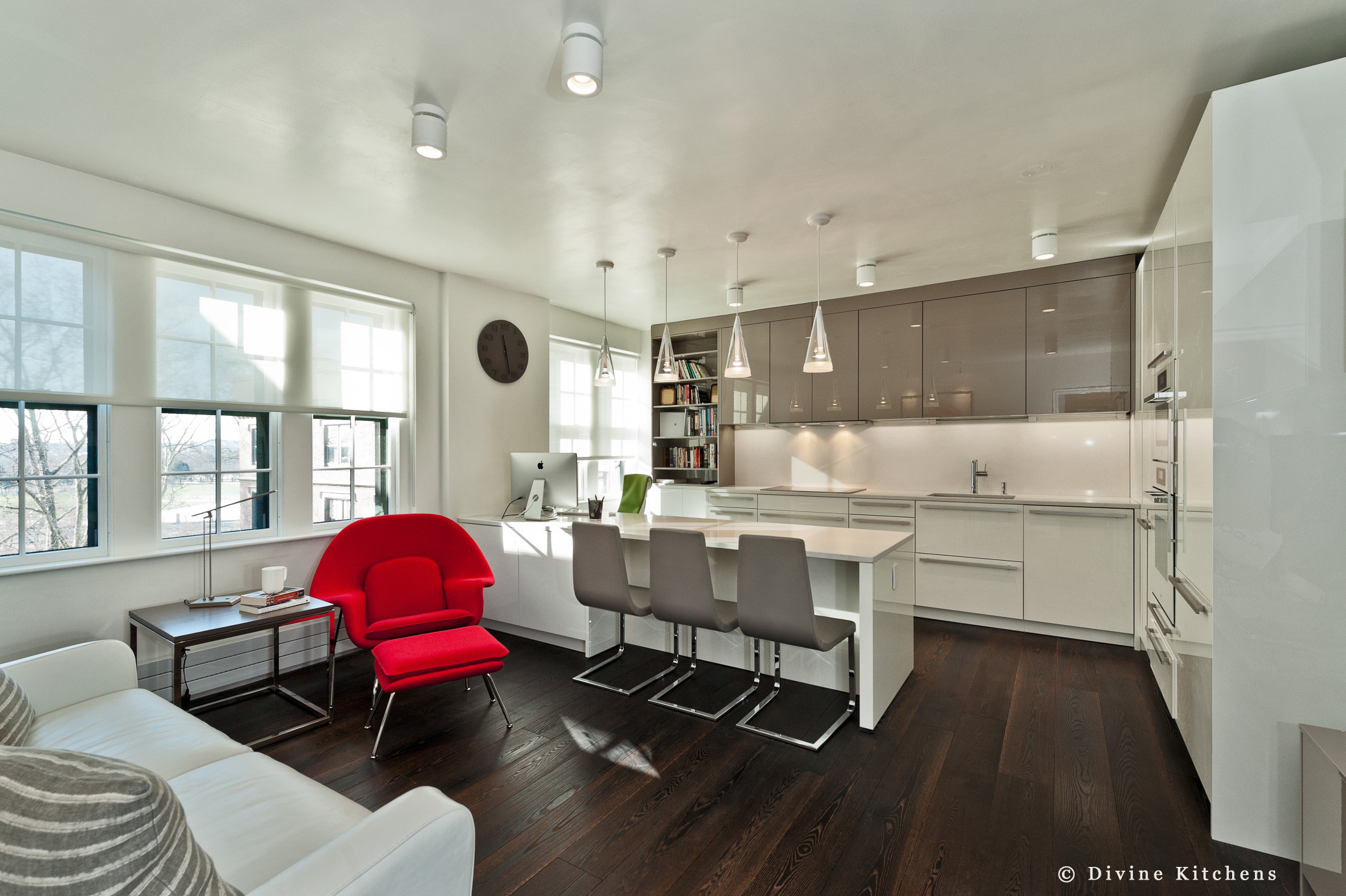 Modern leicht kitchen with white and grey high gloss lacquer cabinets. Red Eames womb chair. Peninsula island with small office area. Miele wall appliances in white.
