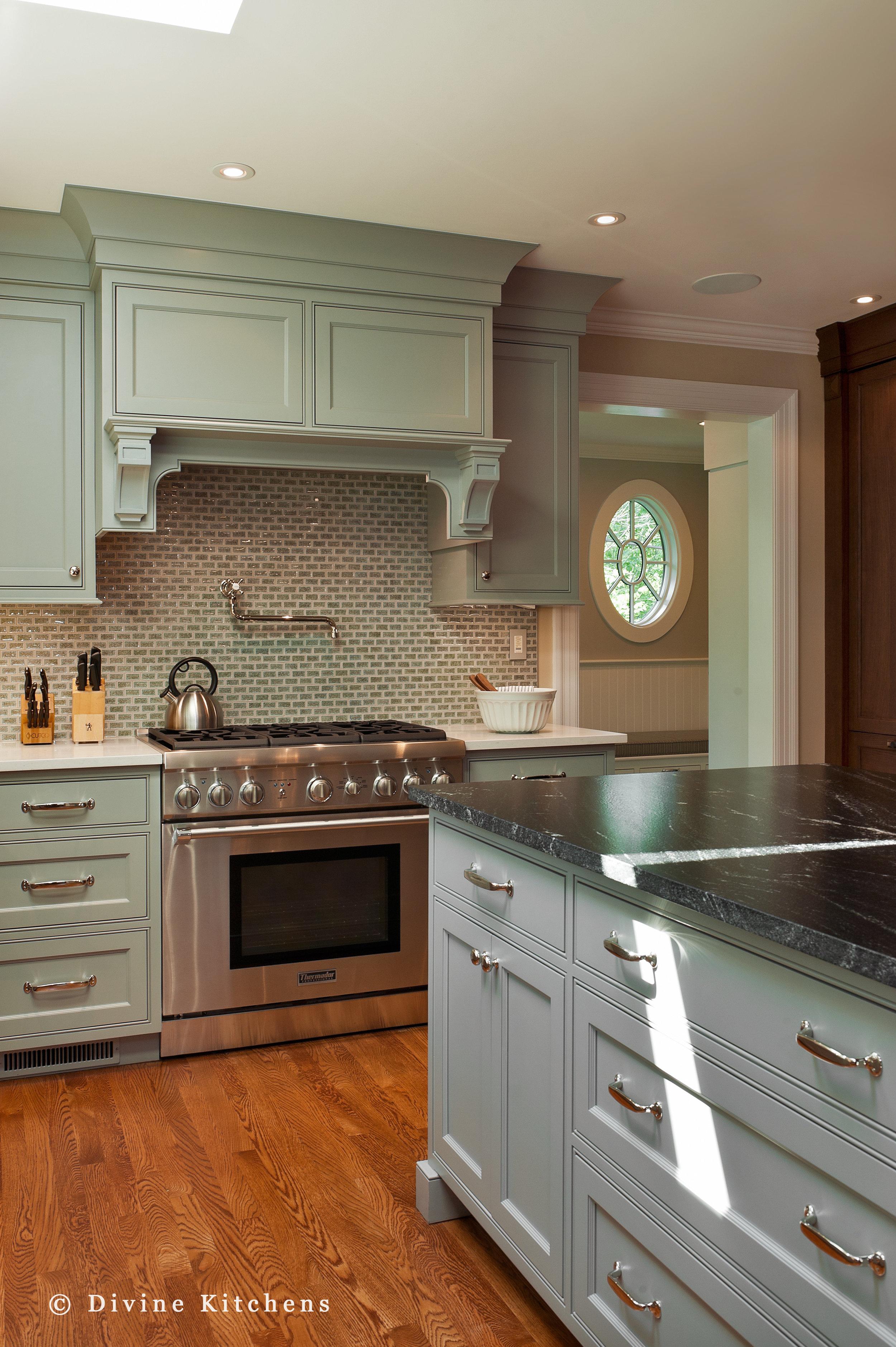 Traditional kitchen inside a historic victorian home. Large windows. Light blue and dark wood shaker cabinets. Mosaic tile backsplash, wolf appliances. Farmhouse sink.