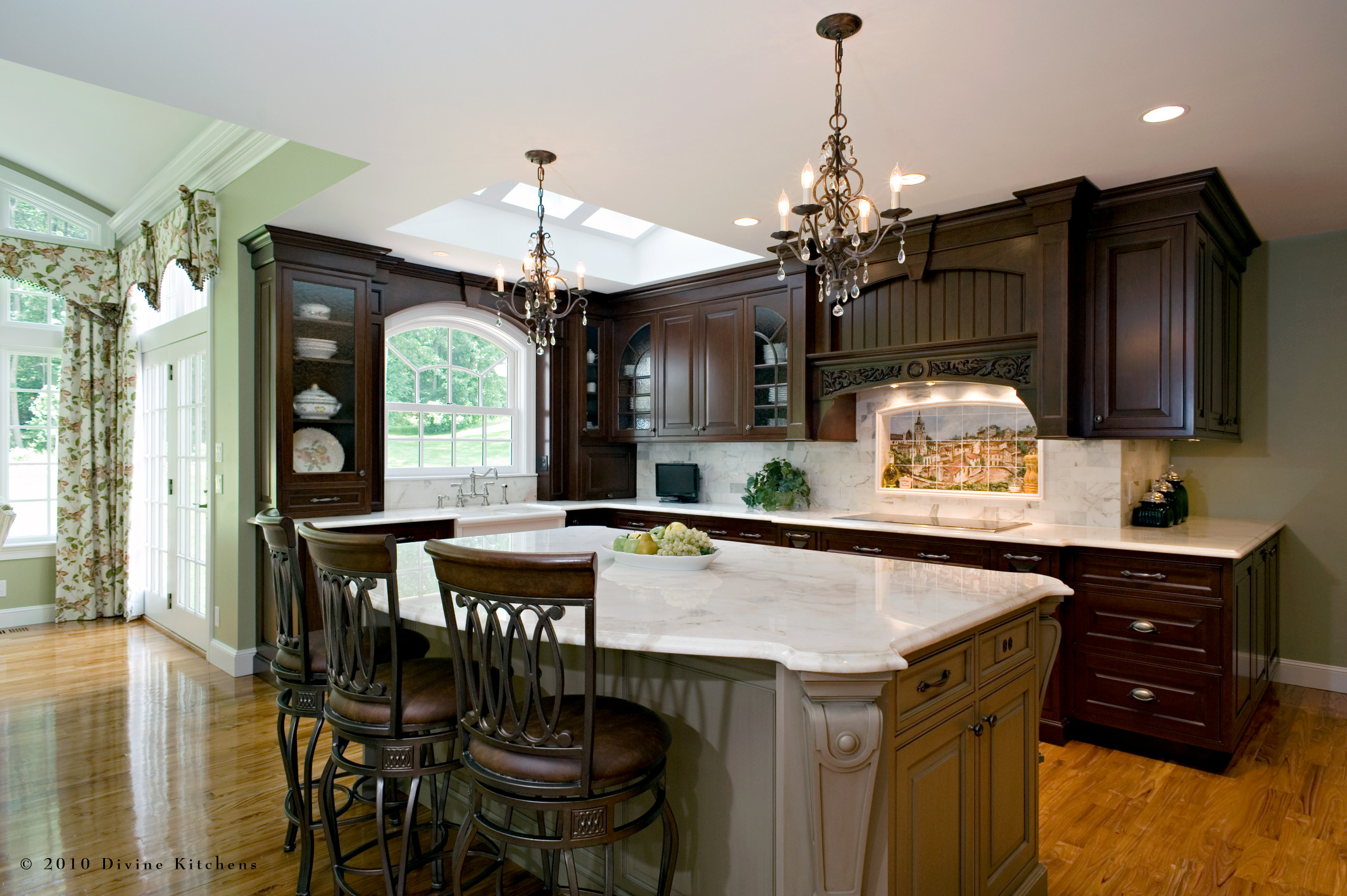 Traditional style kitchen with green and darkwood cabinets. French country inspired design with a mural backsplash. Marble countertops.