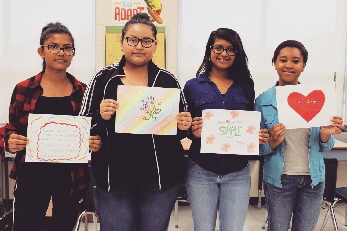 Four students stand smiling in a line, holding hand-drawn posters with positive messages.