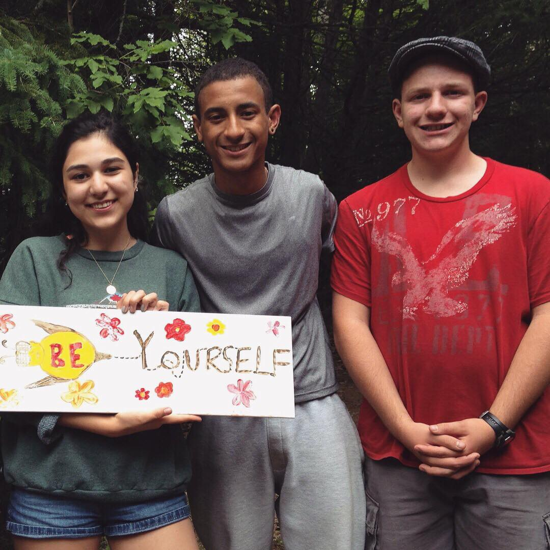 "Three camp staff stand smiling, holding handmade sign that says ""Be yourself"""