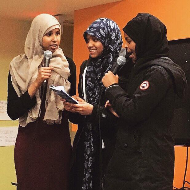 Three high school girls standing together. Two speaking into microphones. Girl in centre is holding a notebook.