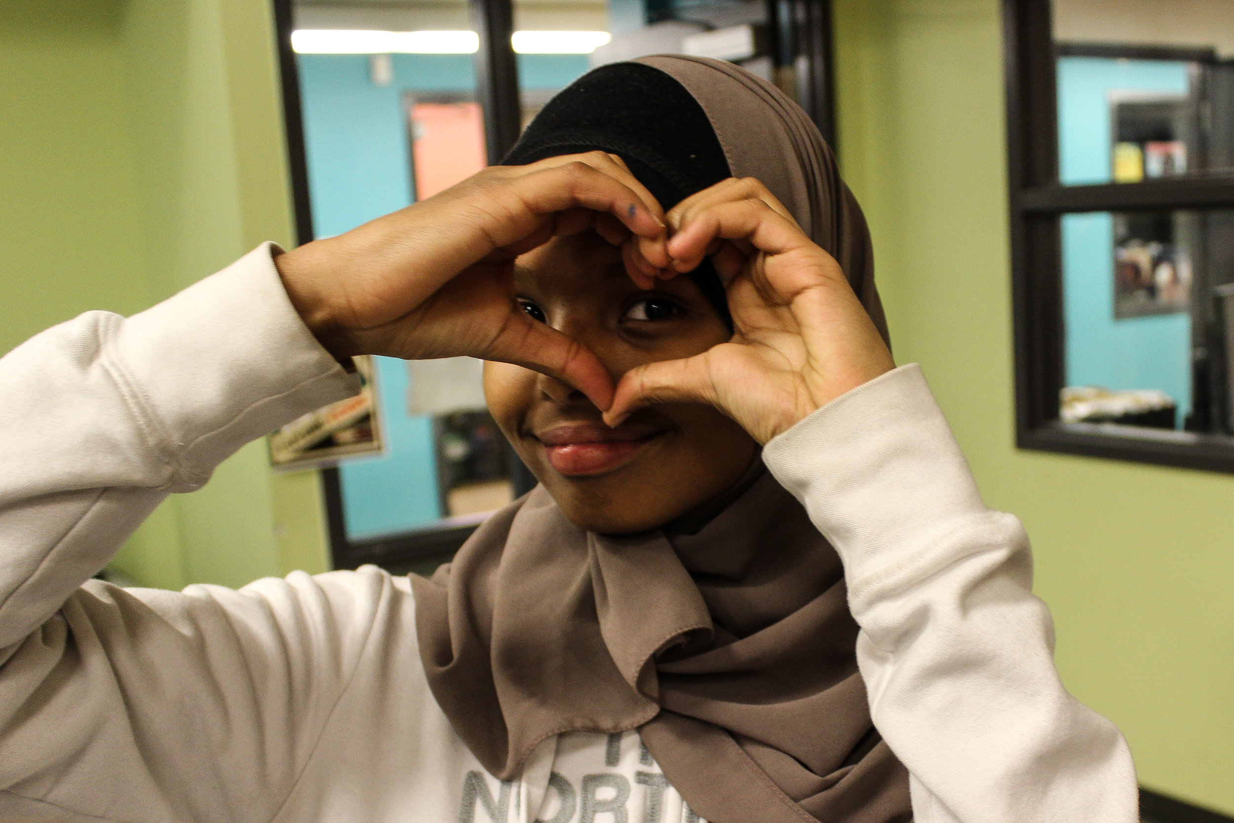 Middle school student making a heart shape with their hands over one eye.