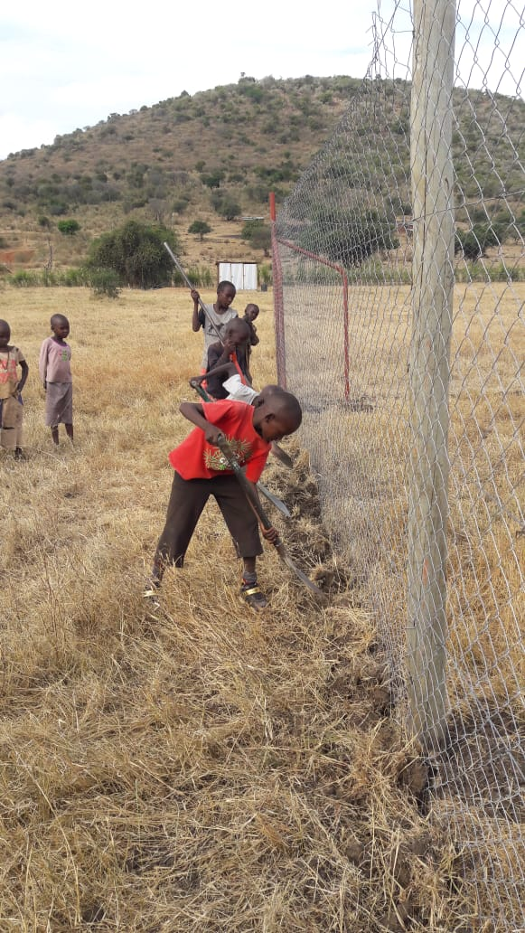 Children helping to build their boma