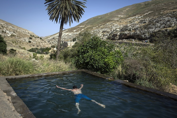 © Tanya Habjouqa (2013) - West Bank: A Palestinian youth from Hebron enjoys a swim in Ein Farha, considered to be one of the most beautiful nature spots in the entire West Bank. It, like many other nature reserves and heritage sites in the West Bank, is managed by the Israeli Nature and Parks Authority. Palestinian touristic enterprise is not allowed.