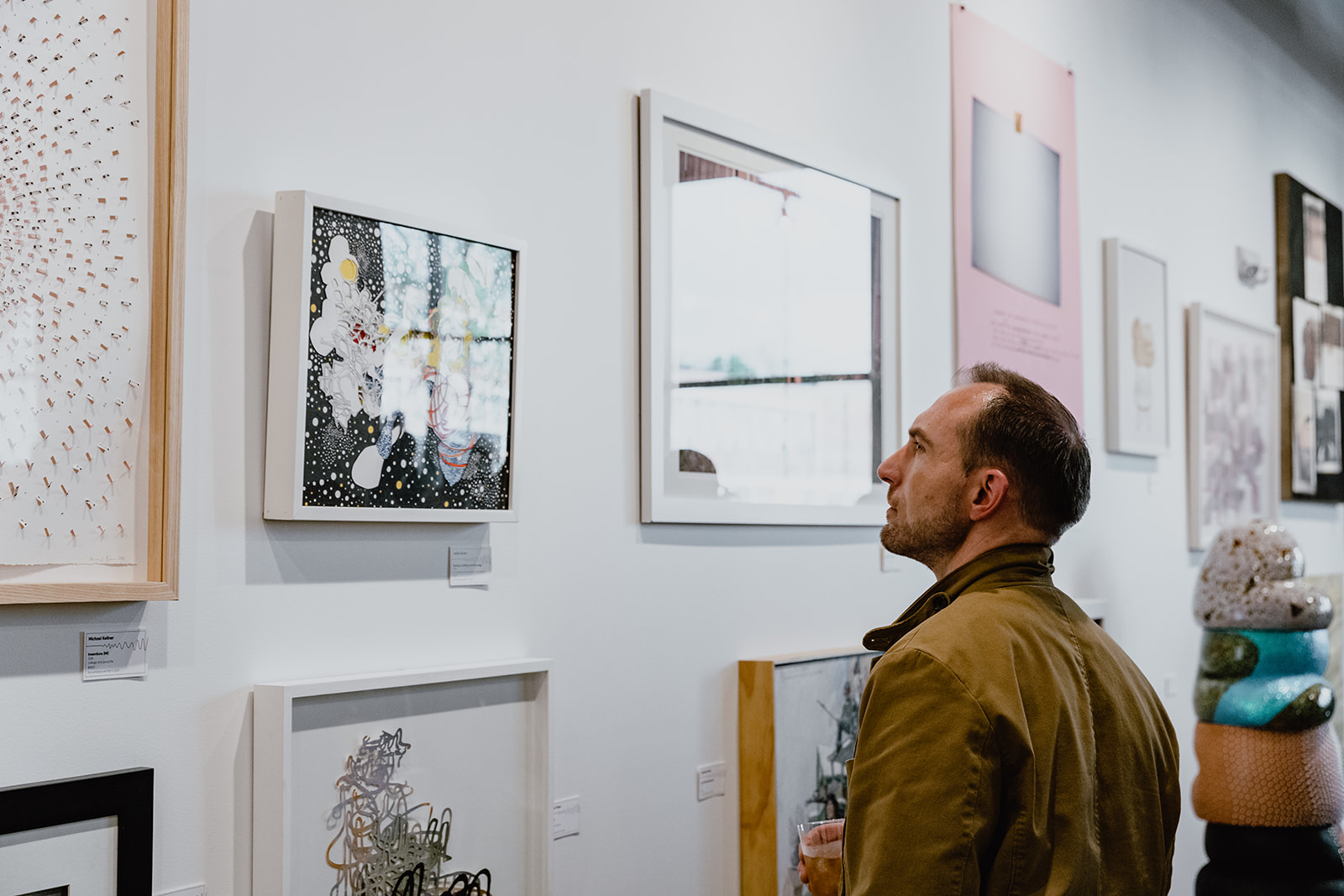 From the right: image of a man in a tan jacket with an amber drink in his hand looking up at the wall of artwork in front of him inside ROY G BIV Gallery. Some of the works are distorted by glare but we see a large variety of framed works hung in salon-style: where dozens of works are squeezed onto a wall in the manner of 19th century salons. Behind the man is a stacked ceramic sculptural work of bulbous creations ranging in texture from scaly to sparkly.