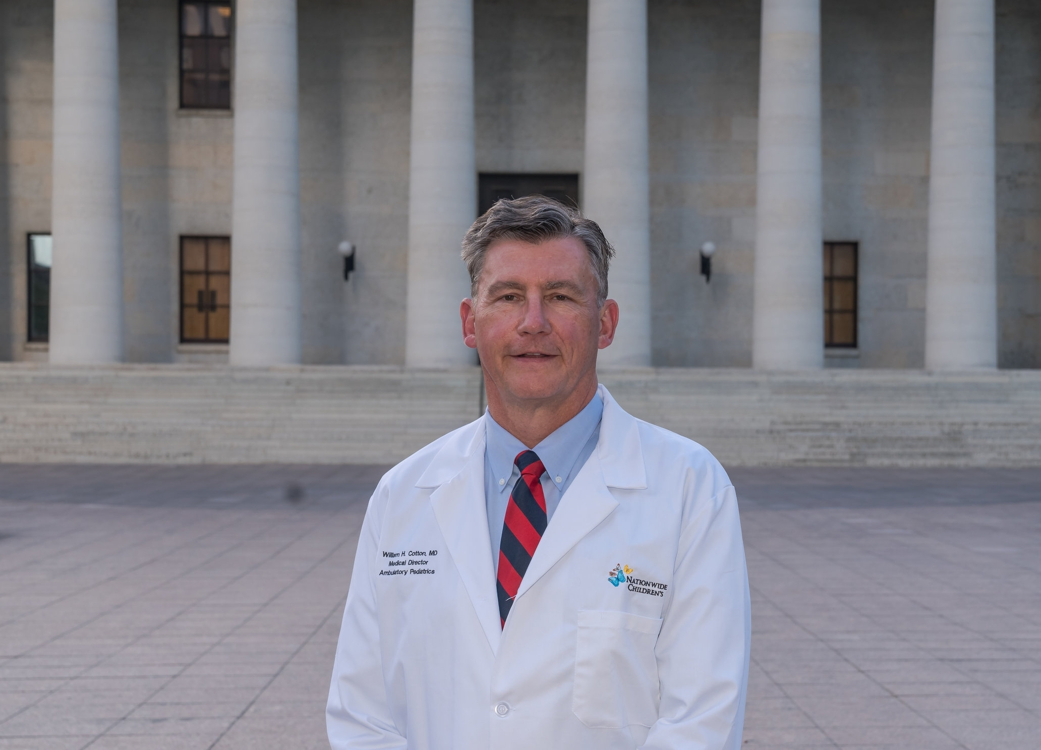 Dr. William Cotton stands in front of the Ohio Statehouse building