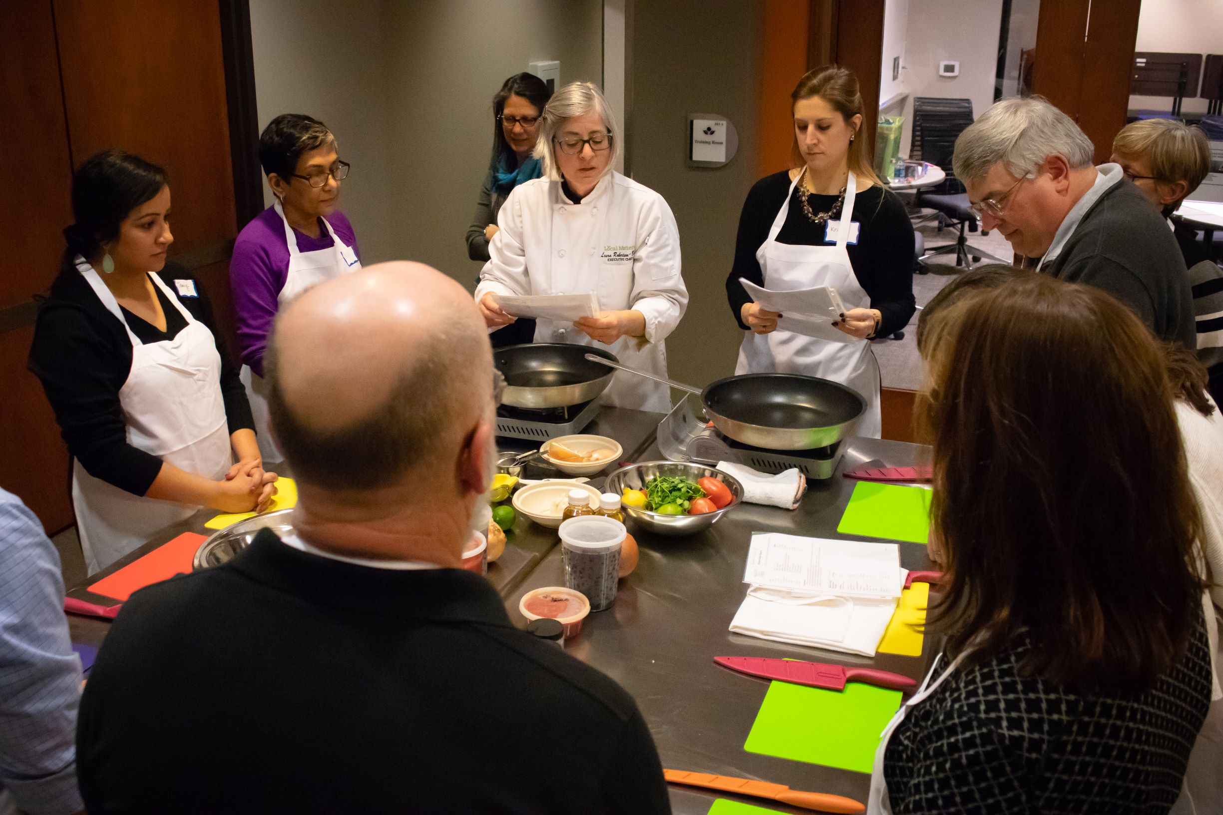 PLA Alumni gather around the chef's table, awaiting instructions from Local Matters chef Laura Robertson-Boyd.
