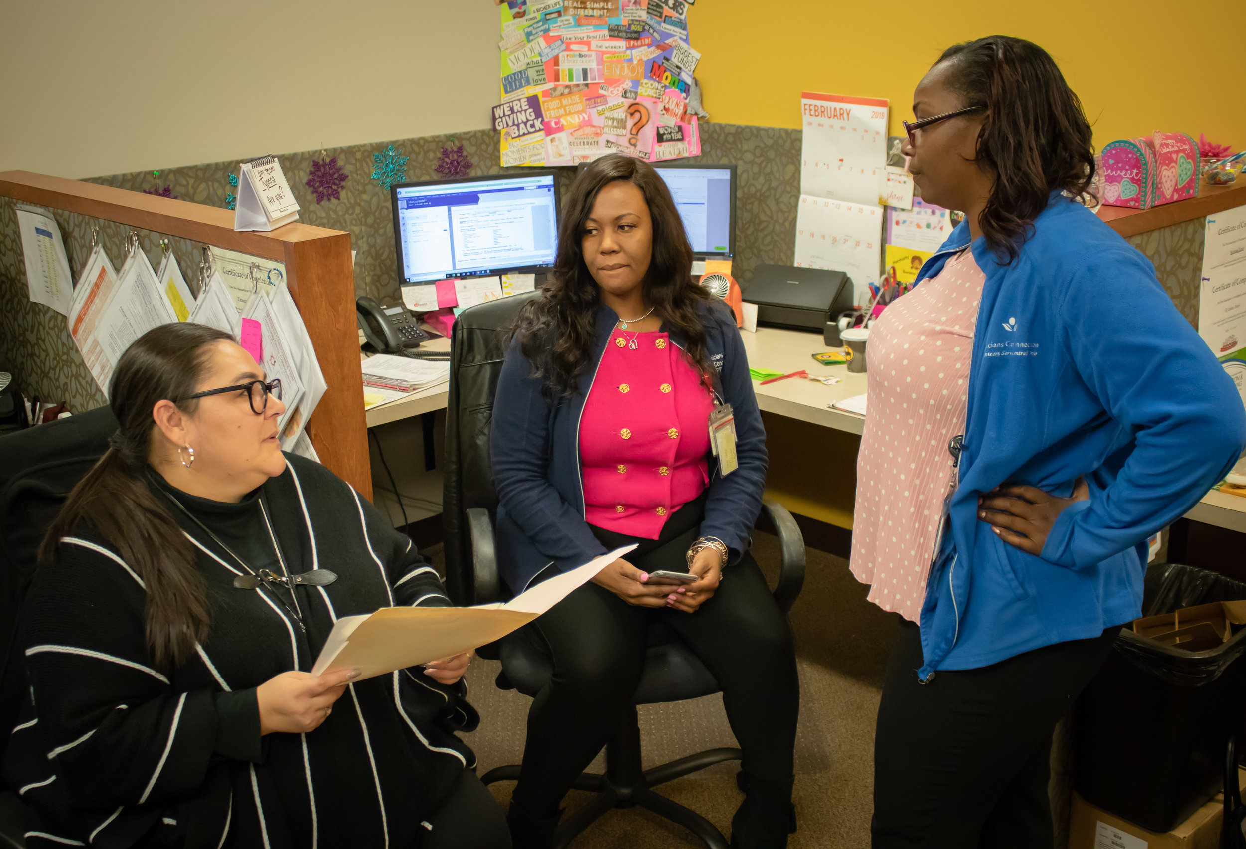 Yesenia Rodriguez (left) discusses a patient's case with her coworkers.