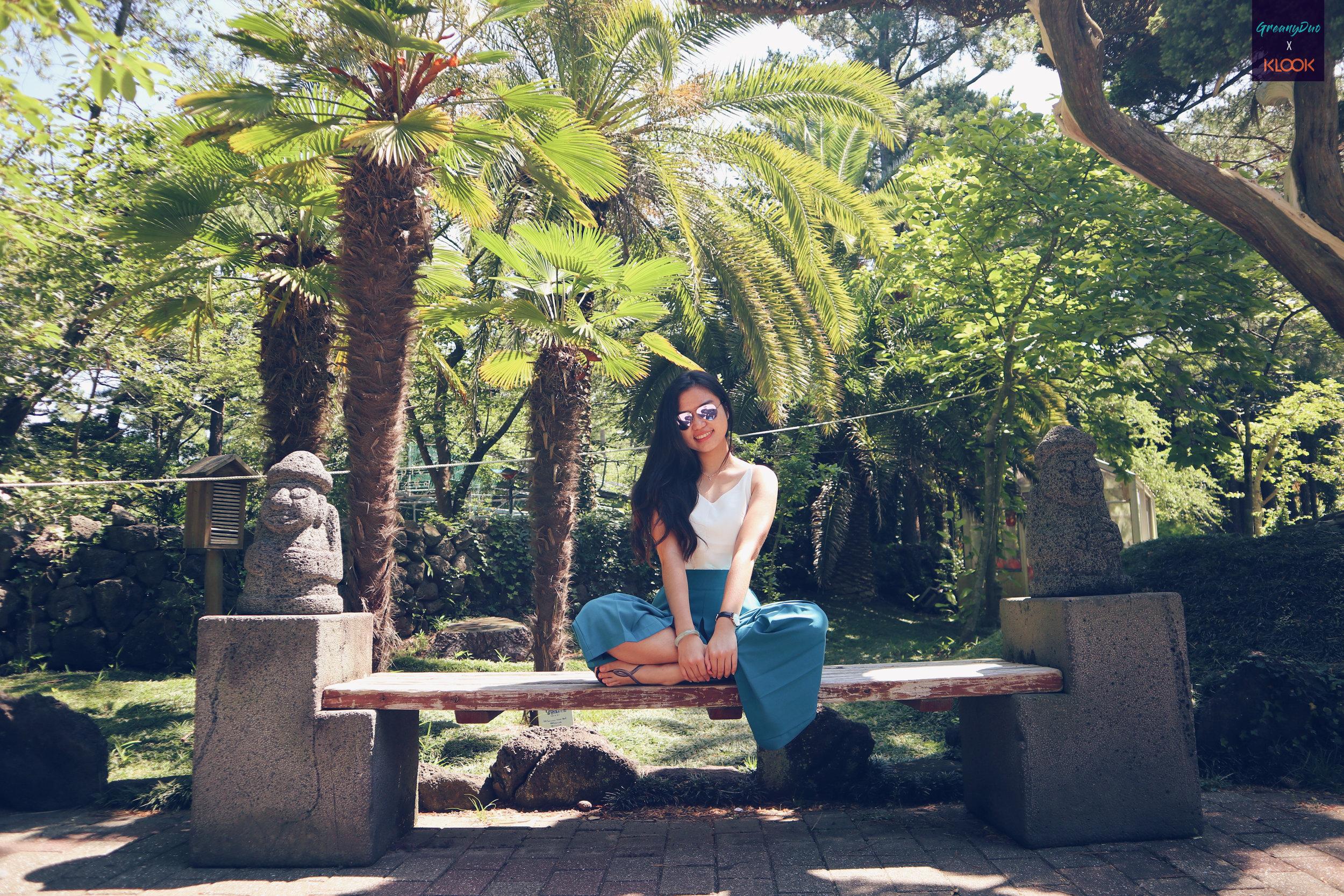 tina posting on a bench at hallim park, jeju