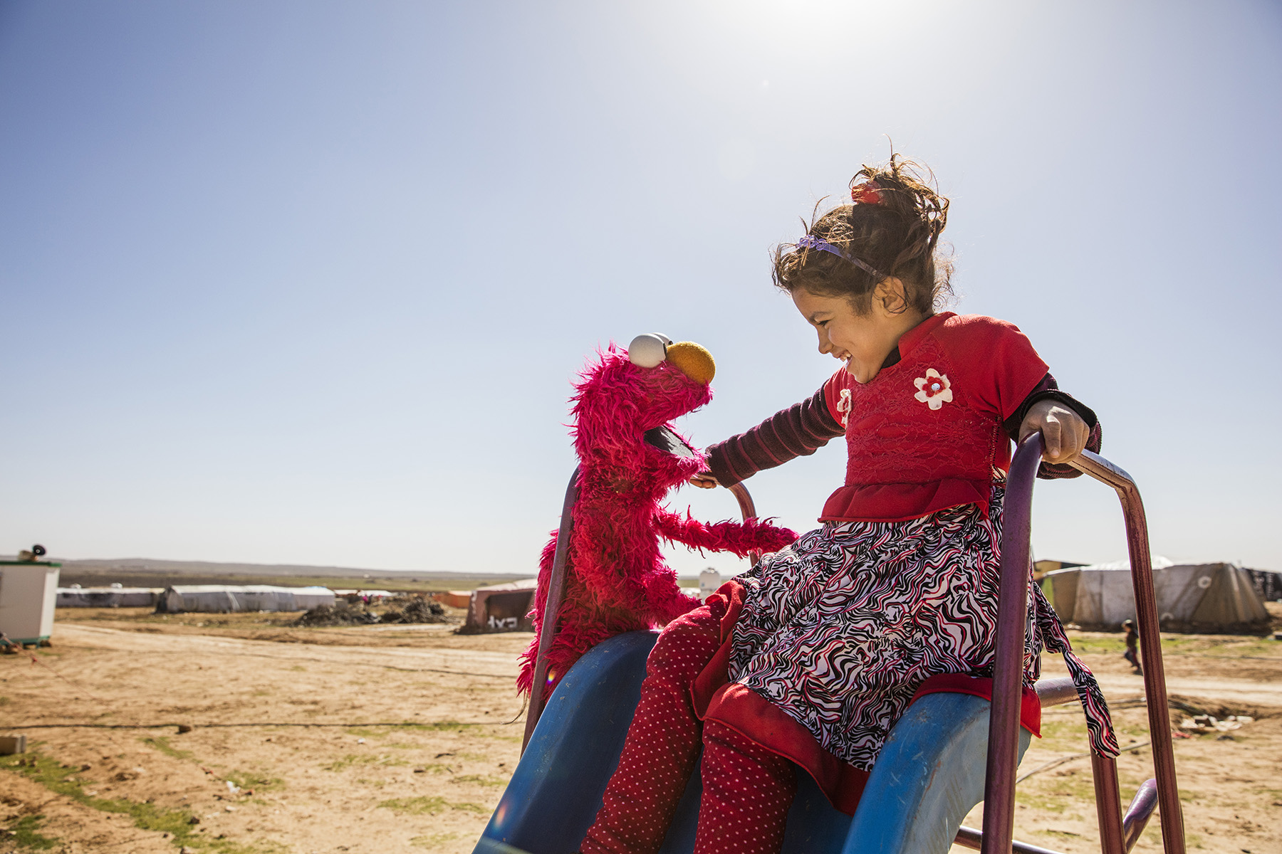 Elmo and a refugee girl in Jordan. Sesame Workshop reaches vulnerable and disadvantaged children in more than 150 countries with pre-primary education.    © Sesame Workshop/Ryan Heffernan