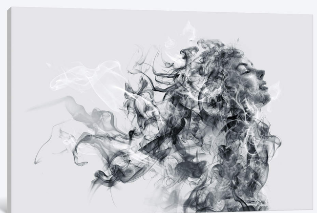 """iCanvas - Canvas - Kiara  This combination of black-and-white photography and abstract art is titled """"Kiara"""". A mass of black, white, and gray wisps that are reminiscent of smoke work their way up toward the top of the picture, dispersing as if blown by the wind. At the edge of the mass, a beautiful woman's face peeks out. Her chin is lifted toward the sky as she smiles gently. This intriguing piece would be excellent in a living room or office."""