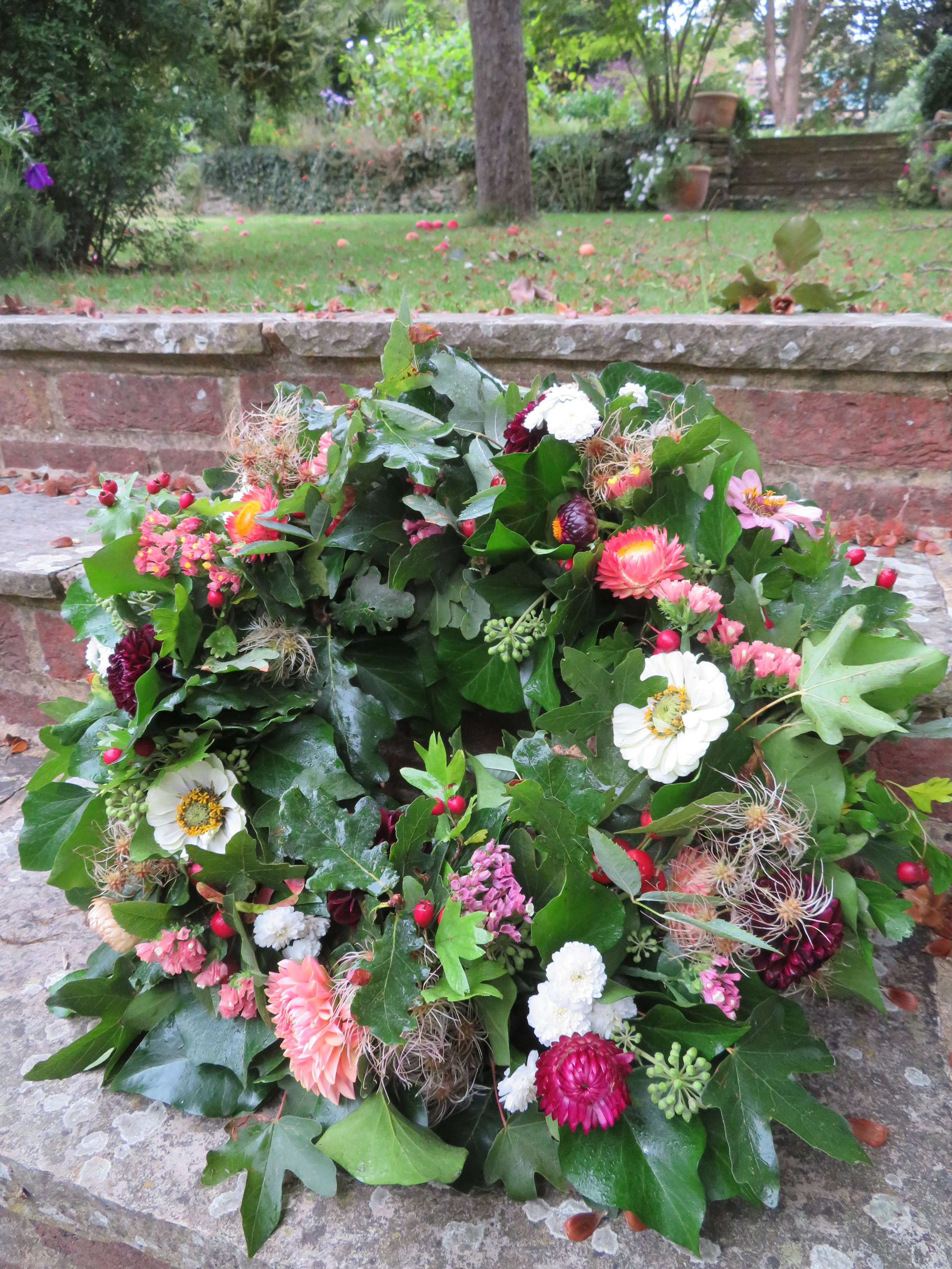 Red berries and long-lasting flowers added in a colour scheme of green, peach and burgundy