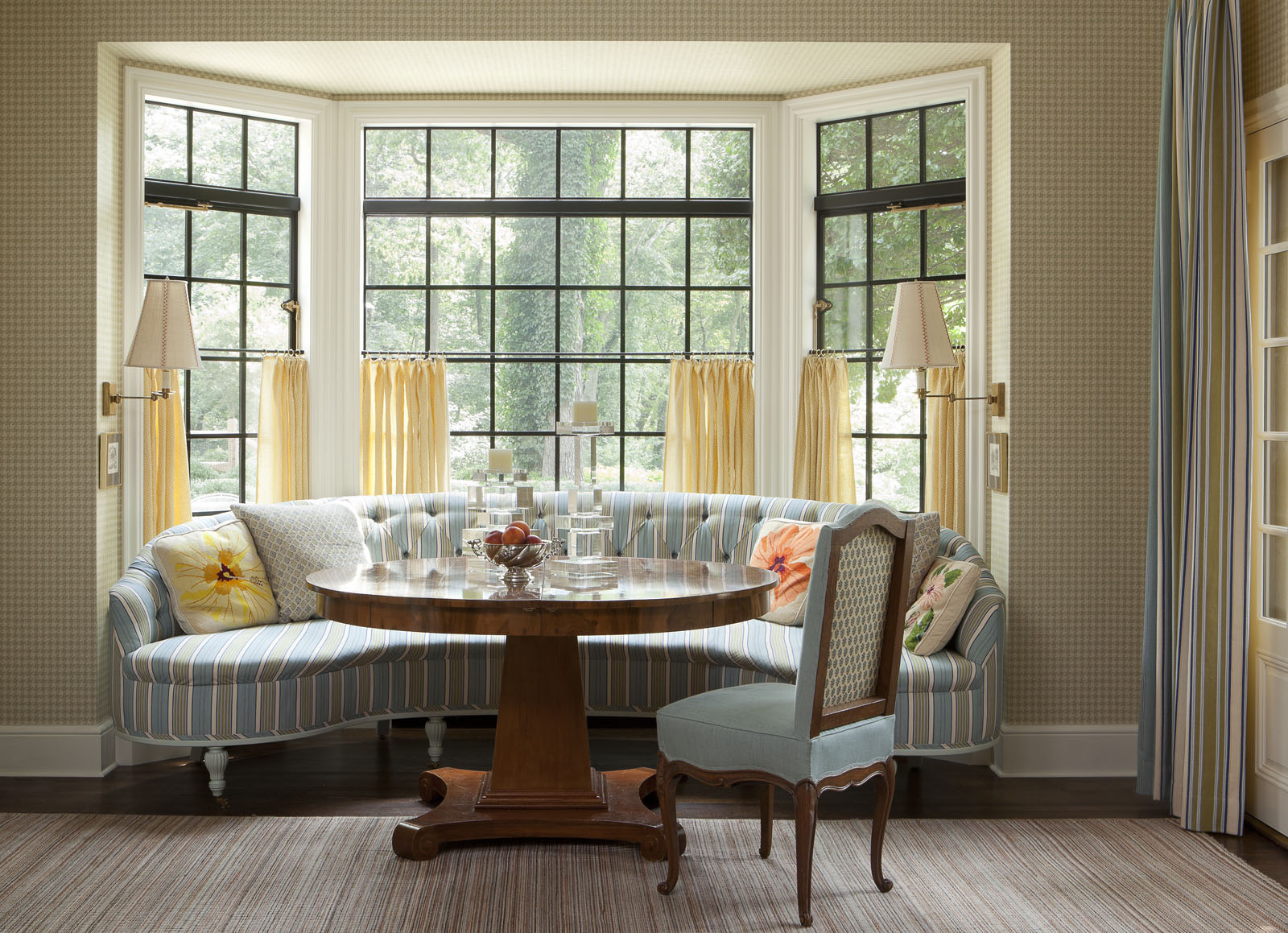 The breakfast room offers a sunny spot for casual meals. Isbell designed the banquette and dining table, the sconces are by  Ann-Morris , and the wall covering is a  Schumacher grass cloth.