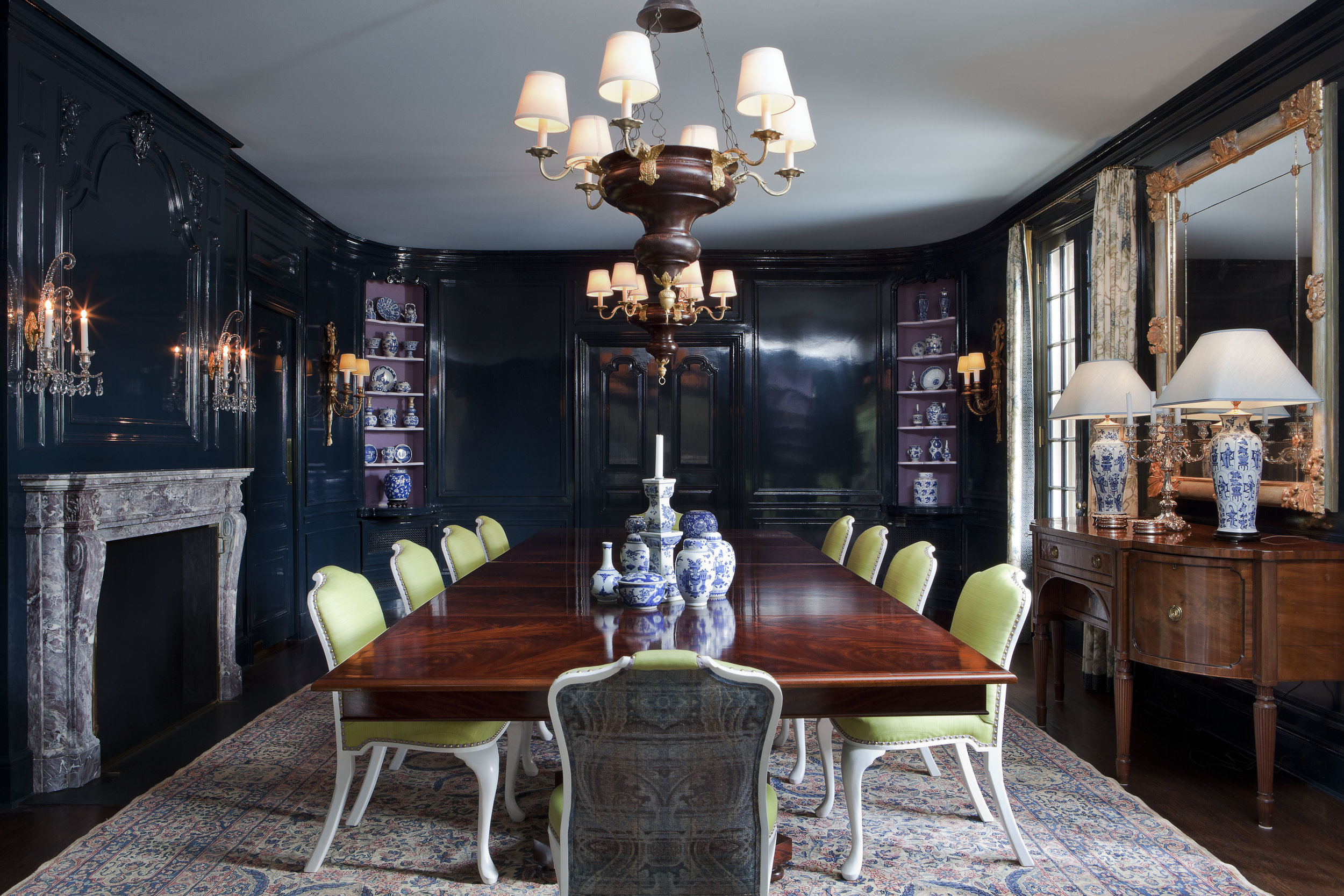 Highlighting the wife's collection of blue-and-white porcelain was a priority in the dining room. The room's walls are coated in a deep indigo lacquer, and the corner niches are lined in lilac burlap. To give the space versatility, Isbell designed two square tables, which can be expanded to create one large table that seats 24.