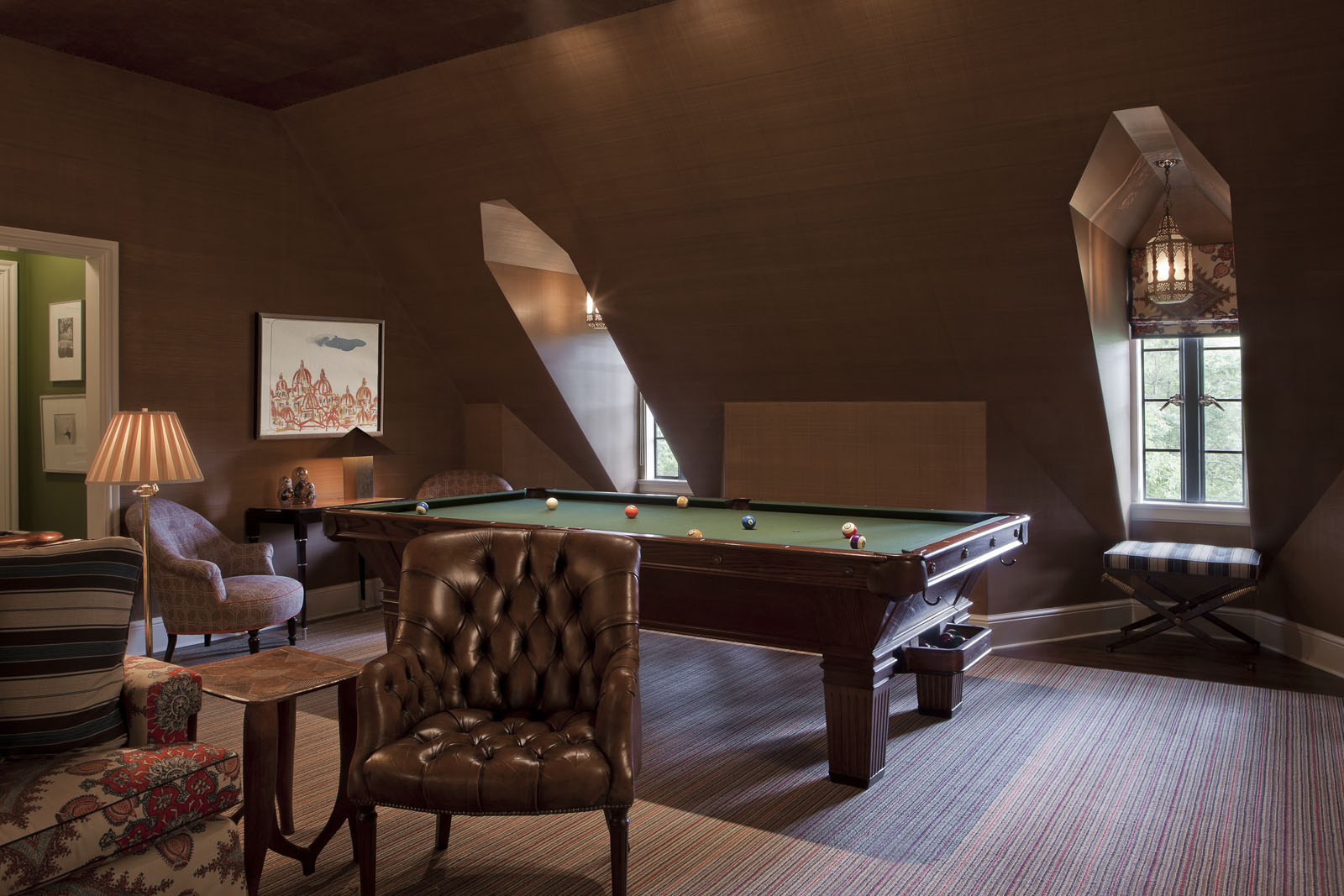 Part of the former staff quarters on the third floor was turned into a billiard room. The early-20th-century library chairs, vintage pool table, and leather-tiled ceiling add to the clubby atmosphere.