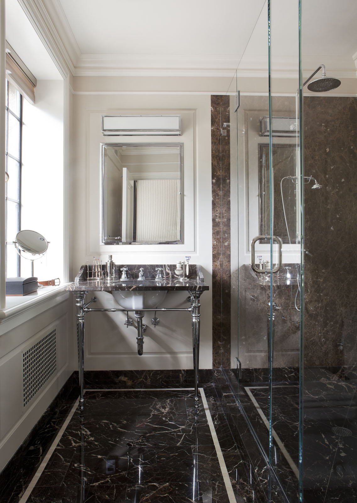 The husband's sleek bath features a wall light by  Circa Lighting  , an  Urban Archaeology  vanity, and a mirror and shower fittings by  Lefroy Brooks  .