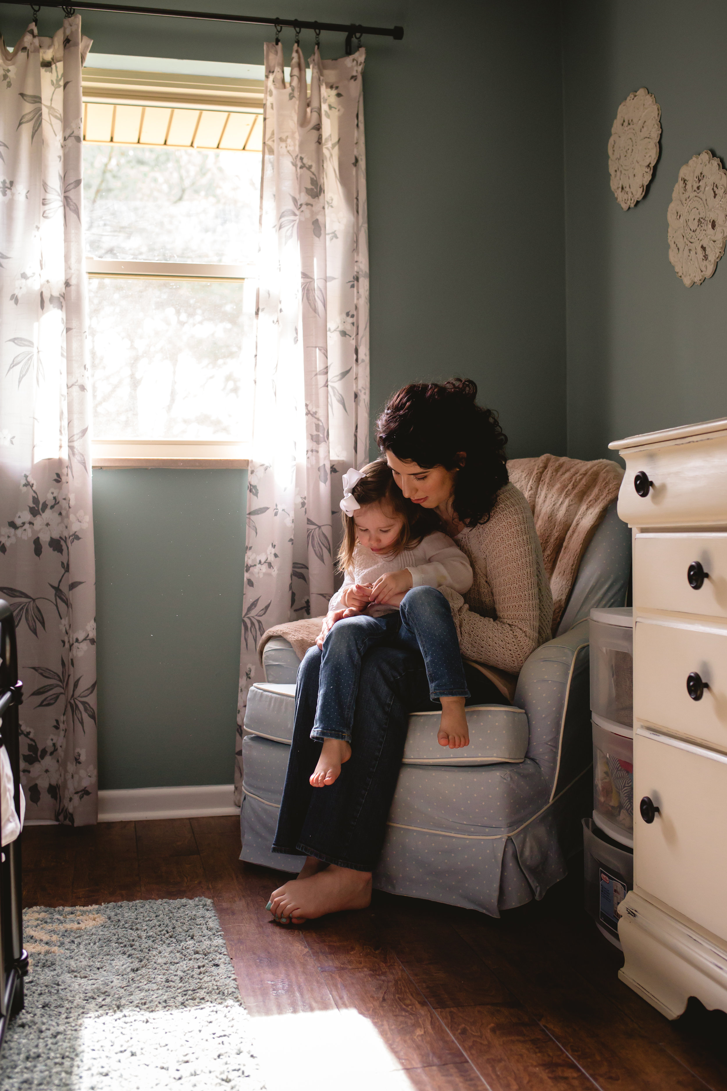 Mother and daughter cuddle in rocker during their Maryville lifestyle session with Brittany Miller Photography