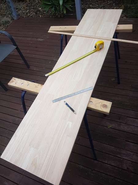 Large plank of wood, measuring tape, ruler and pencil
