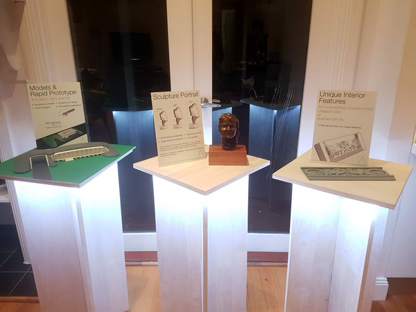 three plinths illuminated from below with sales items on display