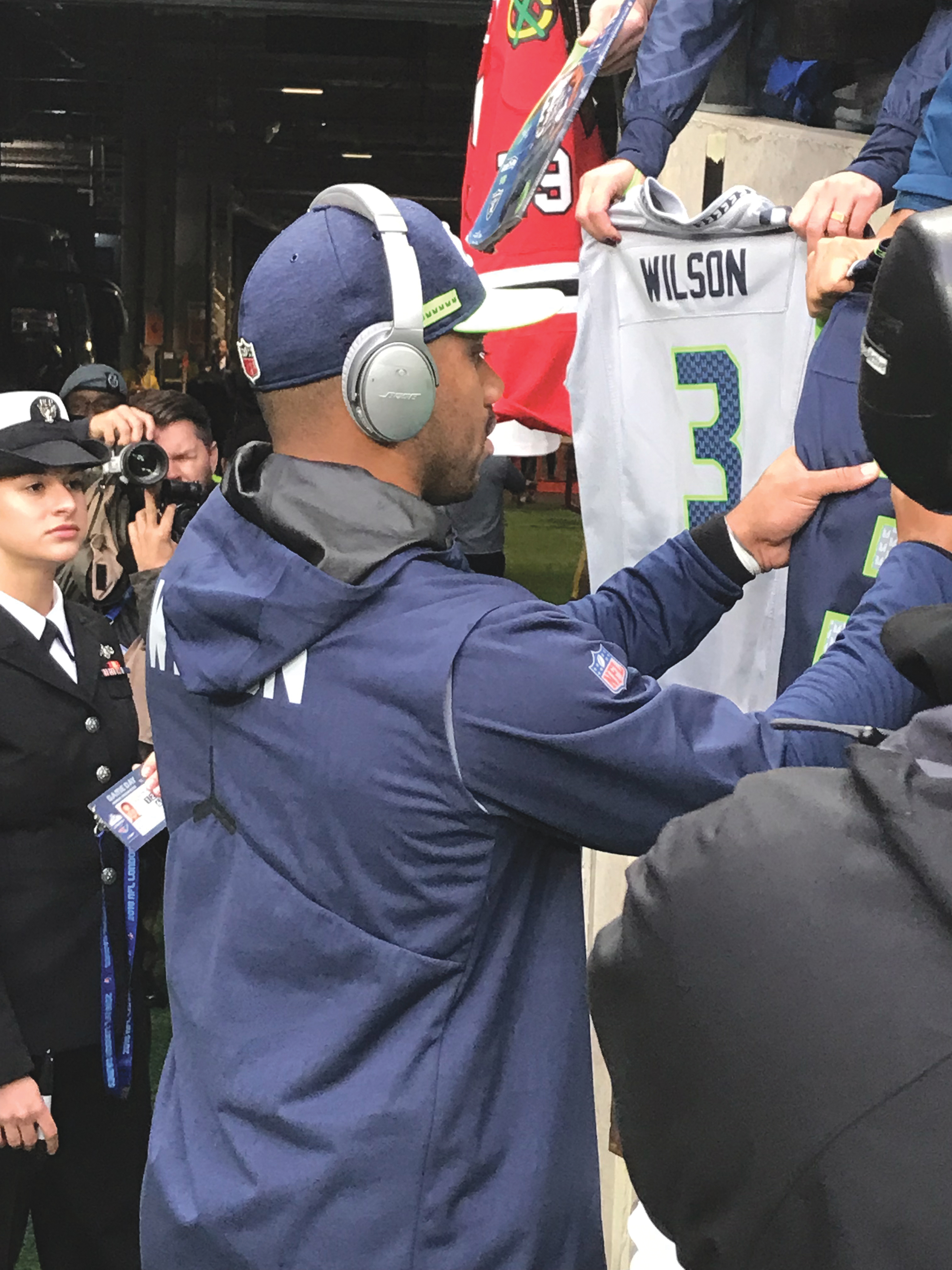 Seahawks Quarterback Russell Wilson signing jersey's prior to kickoff as the Seattle Seahawks were in London to take on the Oakland Raiders. (whatsgoodinsports.com/LA News Observer photo)