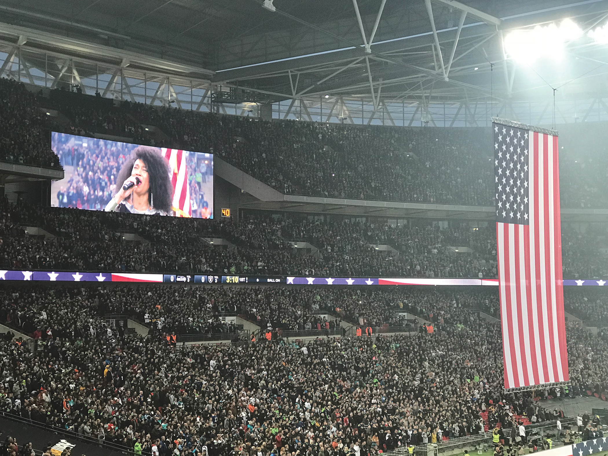 Judith Hill sings the USA National Anthem before a packed house at Wembly Stadium, prior to the Seattle Seahawks vs Oakland Raiders game. (Whatsgoodinsports.com/LA News Observer photo)