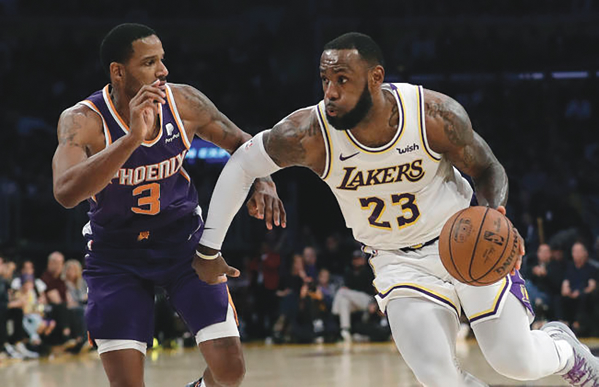 Los Angeles Lakers' LeBron James (23) dribbles next to Phoenix Suns' Trevor Ariza (3) during the second half of an NBA basketball game Sunday, Dec. 2, 2018, in Los Angeles. (AP Photo/Marcio Jose Sanchez)