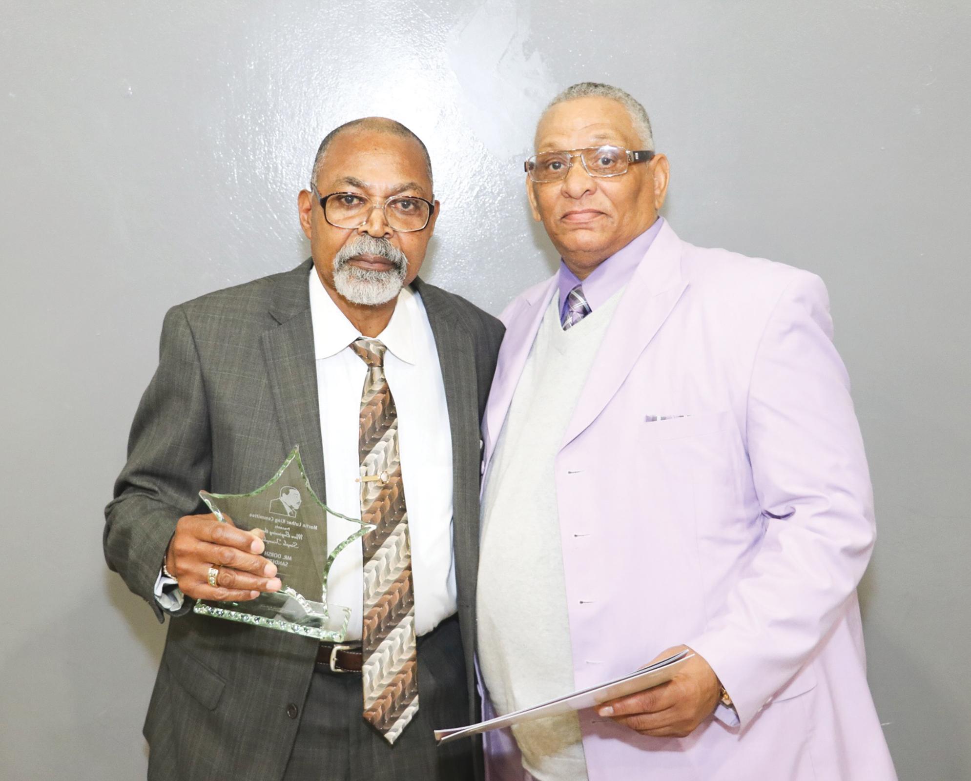 Local Barber Dorsh Sanders (L) accepting the Rev. Martin Luther King Jr. Drumline Major Lifetime Achievement Award. (Carrington Prichett photo)